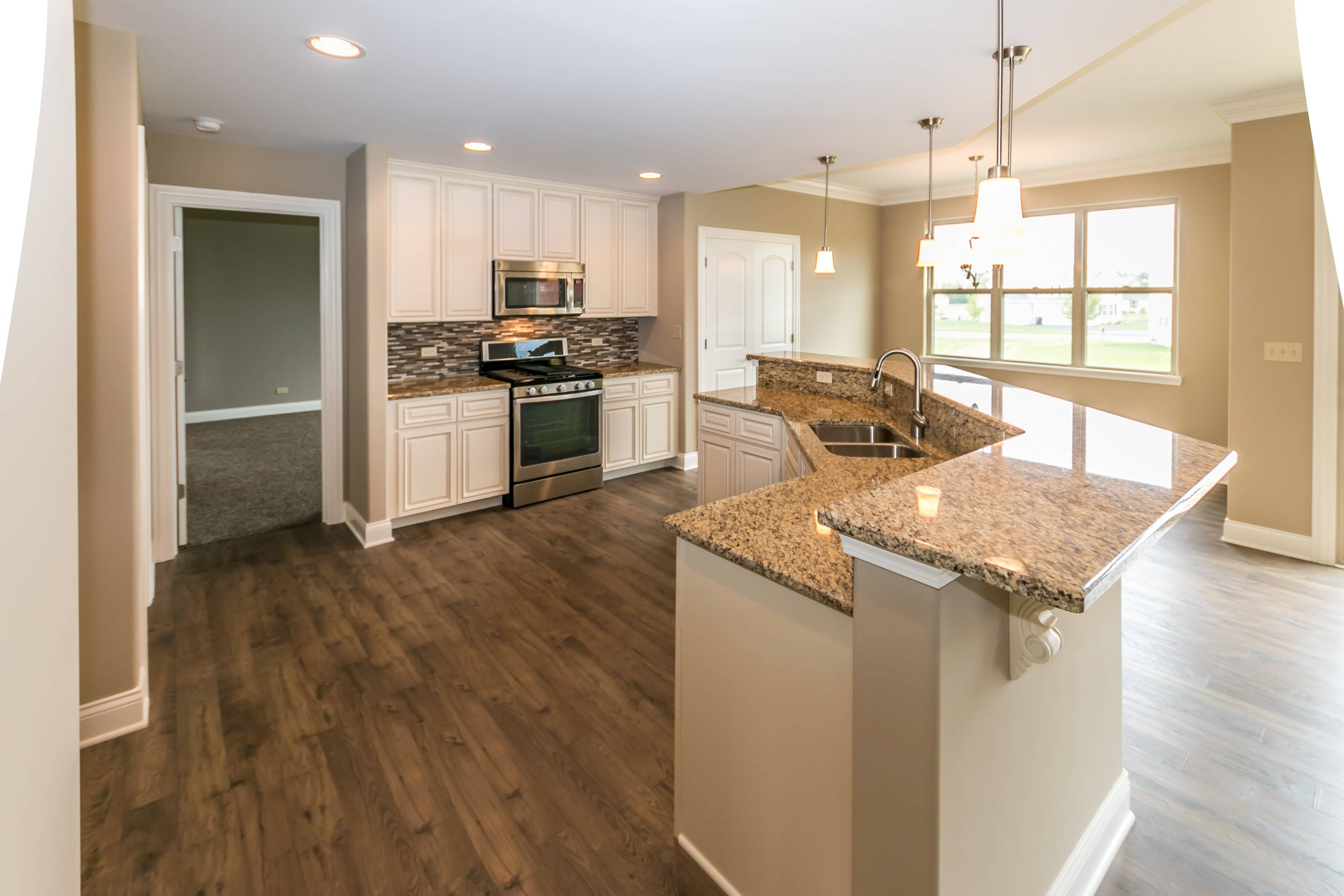 In the Harrison model, the kitchen is open to the breakfast nook with a sink that overlooks the great room and the outdoors.