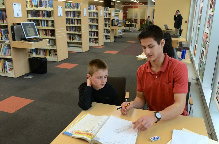 Dylan Sherwin, left, and Matthew Zalewski work on math during a session at Aspen Drive Library. Zalewski launched Epiphamatics, a tutoring company specializing in math support for elementary and middle school students.