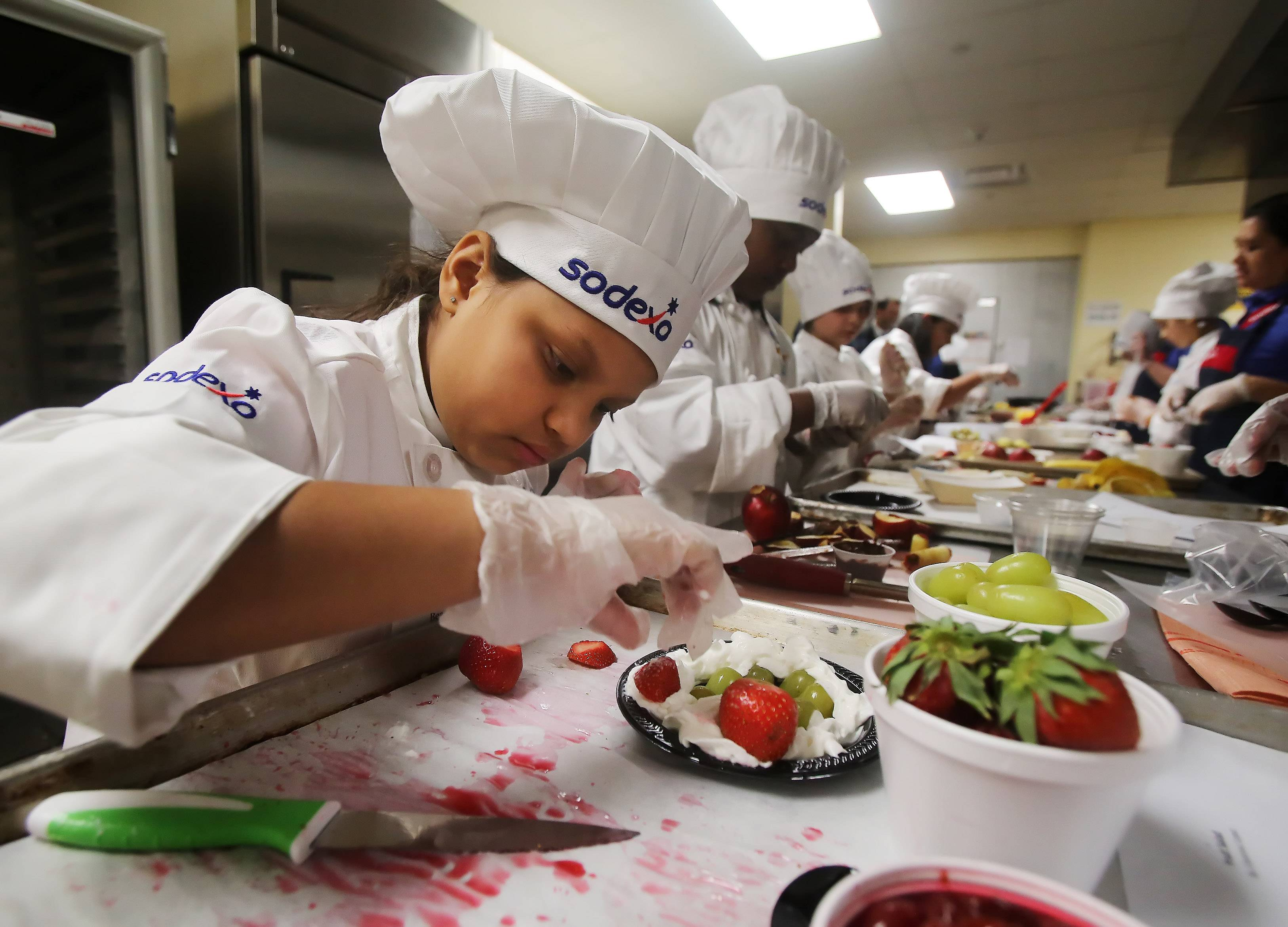 Lilyanna Lopez of Beach School in Round Lake makes a fruit salad during the Sodexo 2015 Future Chefs Challenge on Wednesday. Students created healthy snacks for judges during the competition.