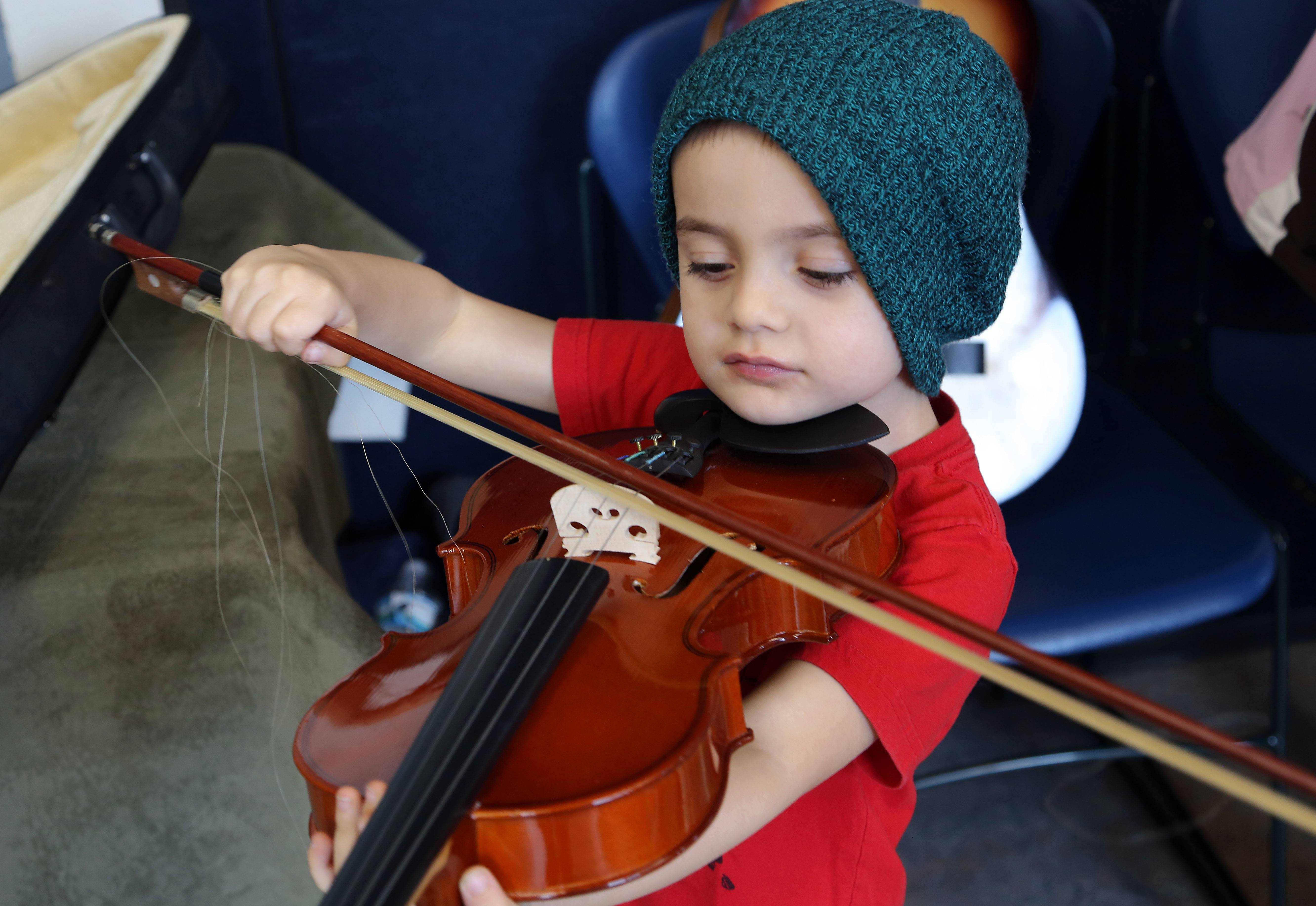 Cooper Laib, 4, of Round Lake Beach tries out a violin Thursday during music instructor Susan Nierman's Instrument Zoo program at Grayslake Public Library.