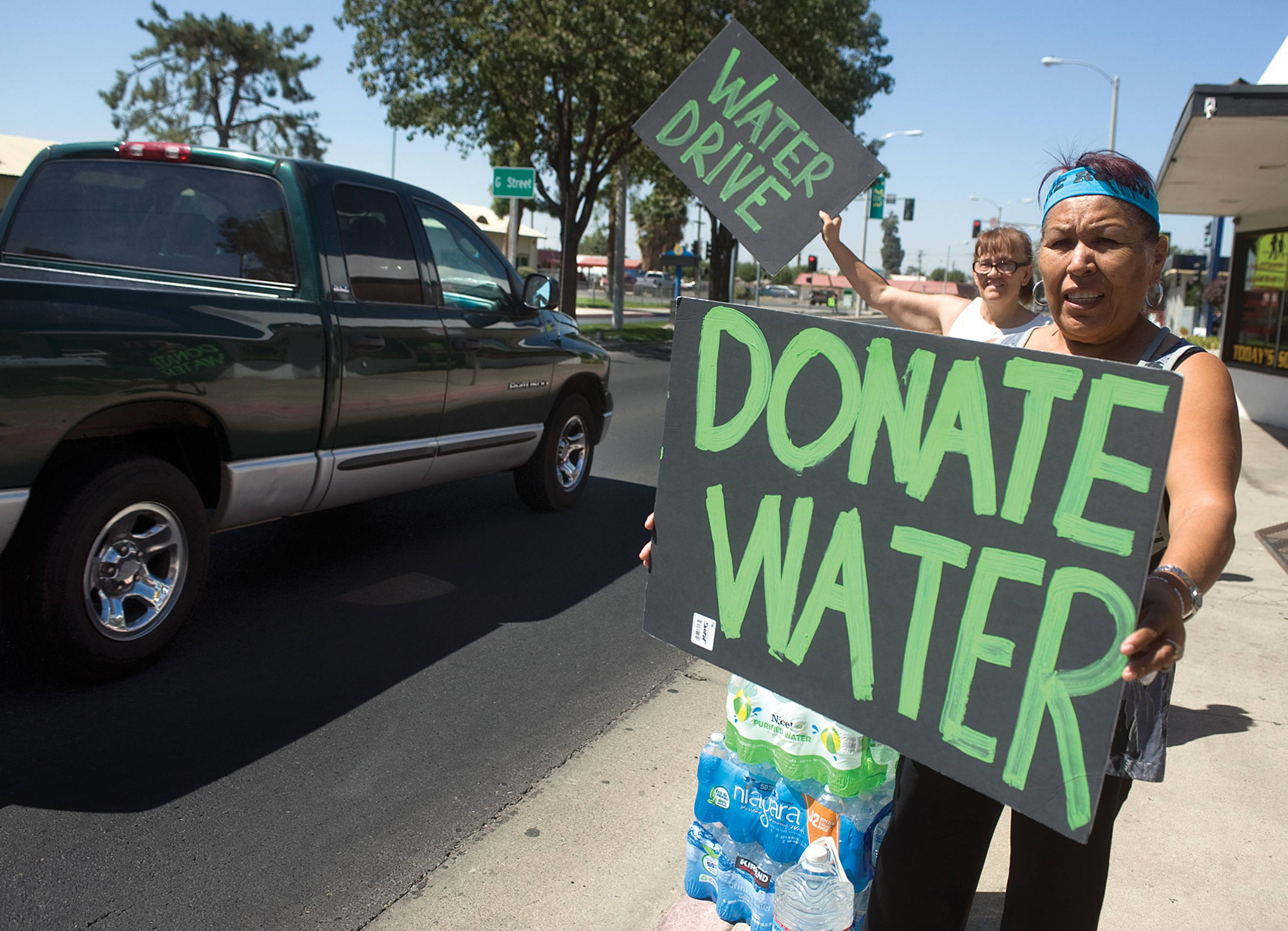 Volunteers appeal to community members for donations at the Porterville Water Challenge on Olive Street in Porterville, Calif. Several locals started their own water challenges to help East Porterville area residents whose wells went dry for months.