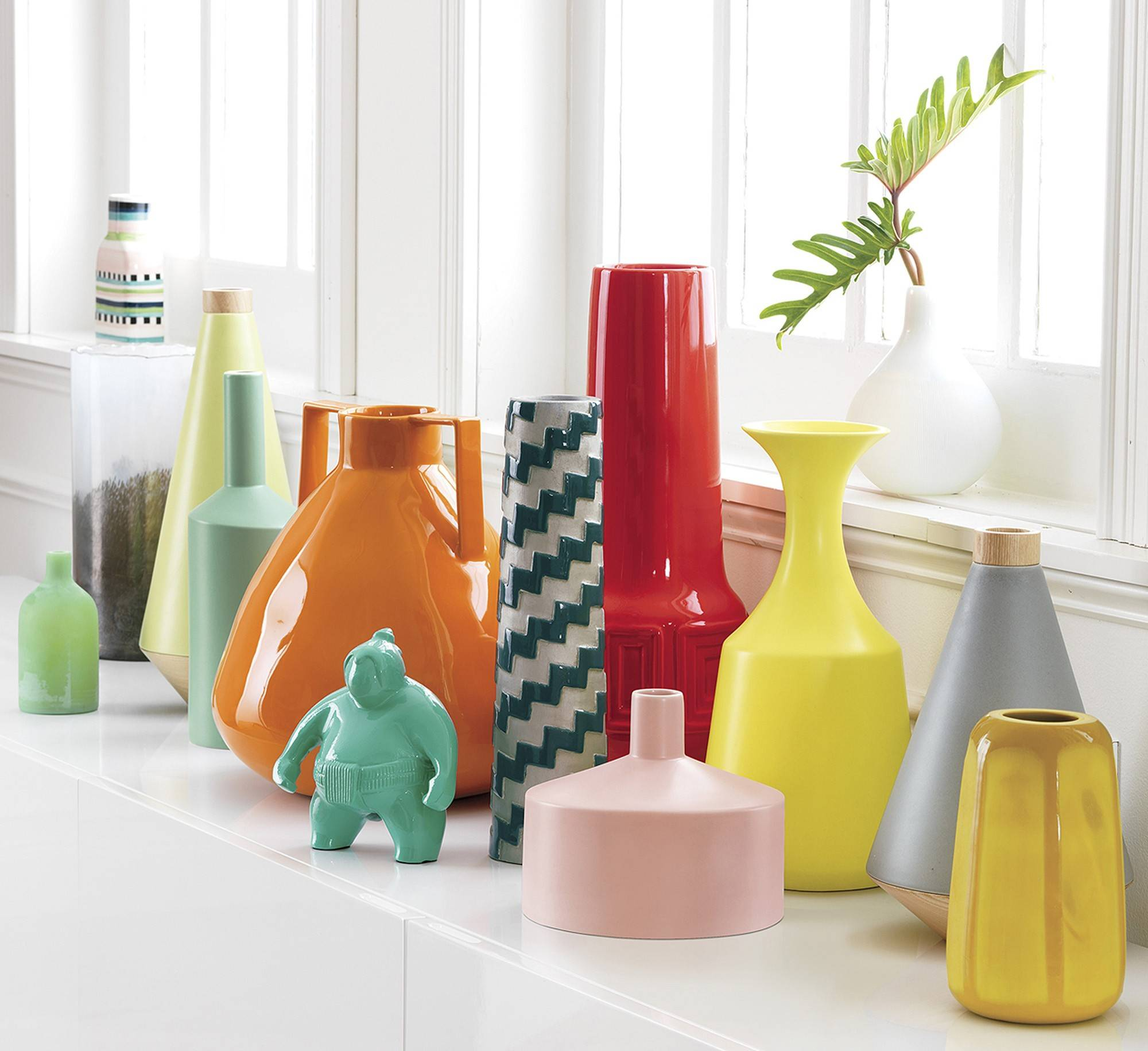 Group colorful sculptural vases of varying sizes on a bookcase, windowsill or table. Check out CB2's Askew vases, from $19.95.