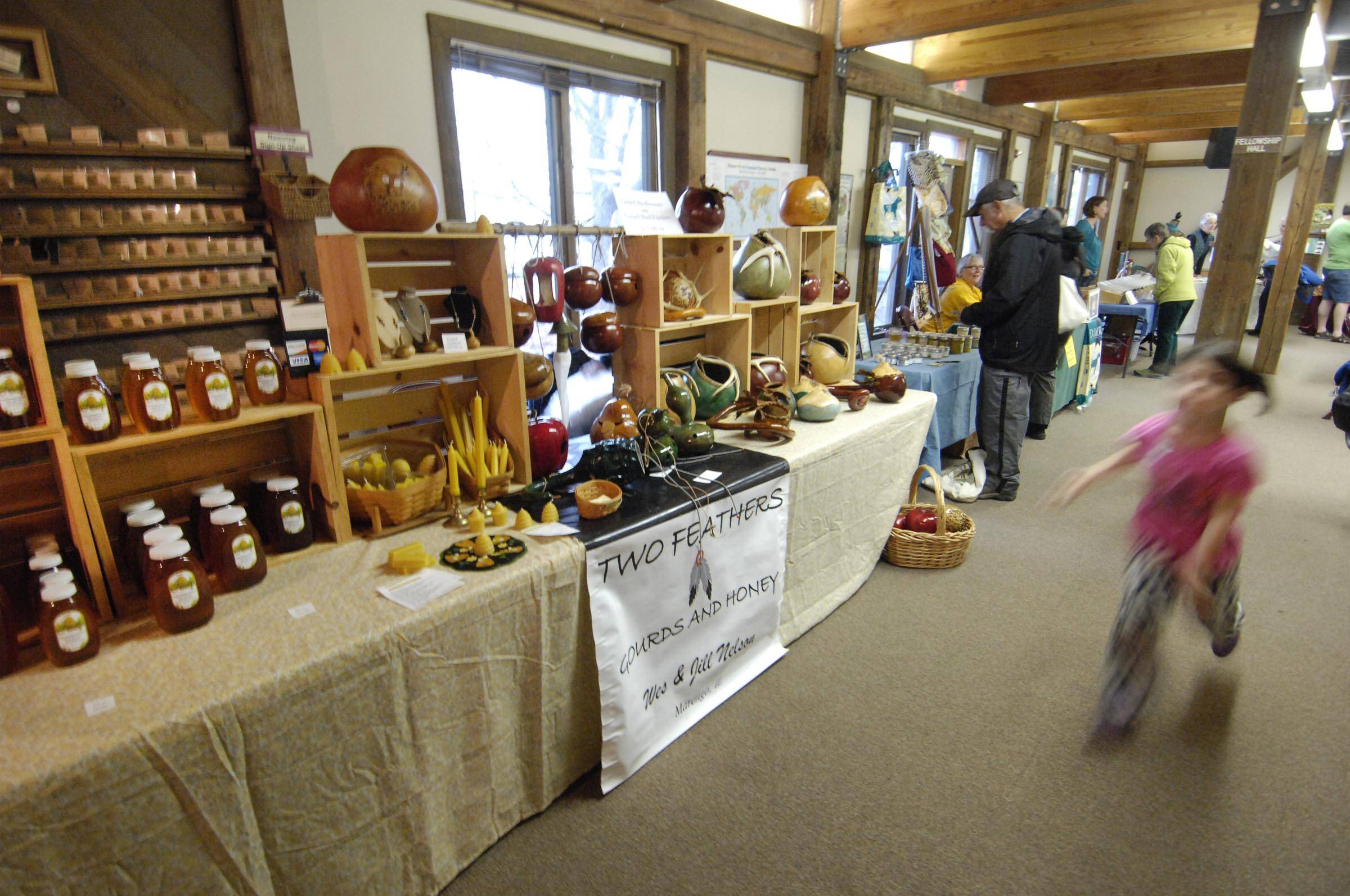 A child runs past the Two Feathers Gourds and Honey booth at a farmers market featuring sustainably produced foods and other items held Sunday at the Unitarian Universalist Church of Elgin. Wes Nelson is a beekeeper and sells honey while his wife, Jill, grows gourds and creates bird feeders and houses with them. They are from Marengo.