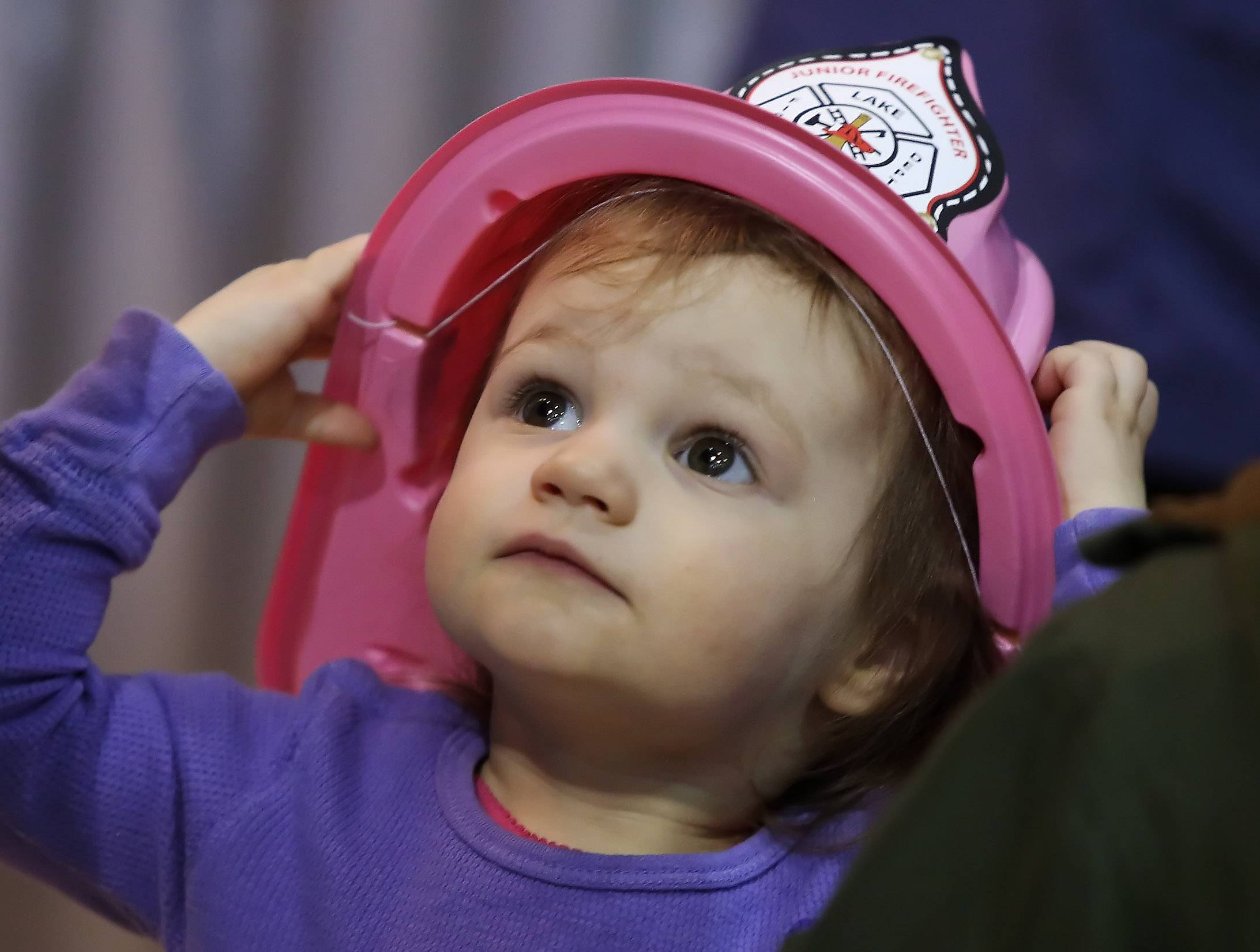Lexi Sparkman, 2, of Round Lake Beach wears a new Lake Villa Fire Department hat she received during SpringFest Expo 2015 on Sunday at Lakes Community High School in Lake Villa. The 12th annual event was sponsored by the Lindenhurst-Lake Villa Chamber of Commerce with 85 businesses participating.