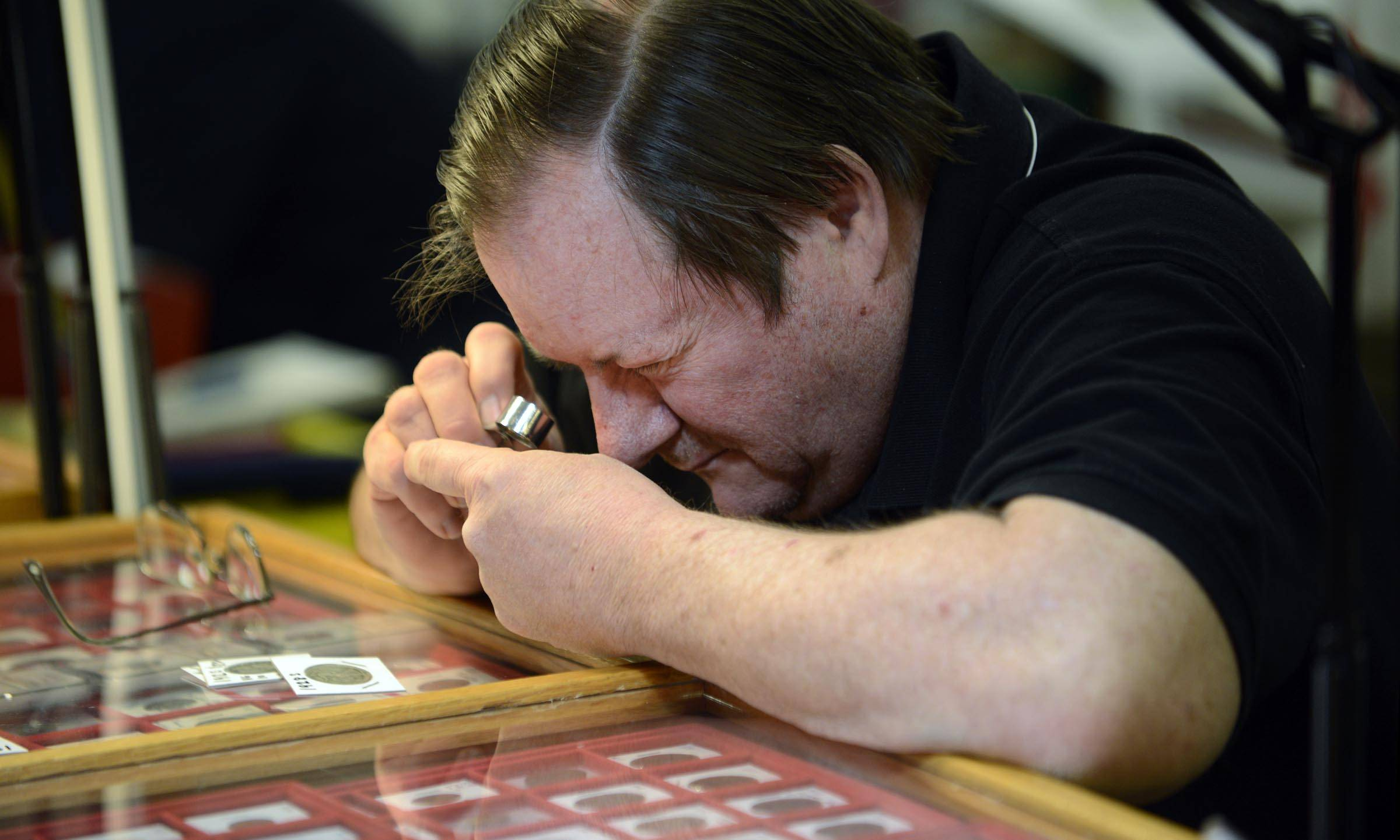 Larry Wolfram uses a loupe to inspect a coin Sunday at the Elgin Coin Club Spring Show at Moose Lodge 799 in Elgin. Wolfram, a club member, owns Wolf Coins & Collectibles of Lockport.