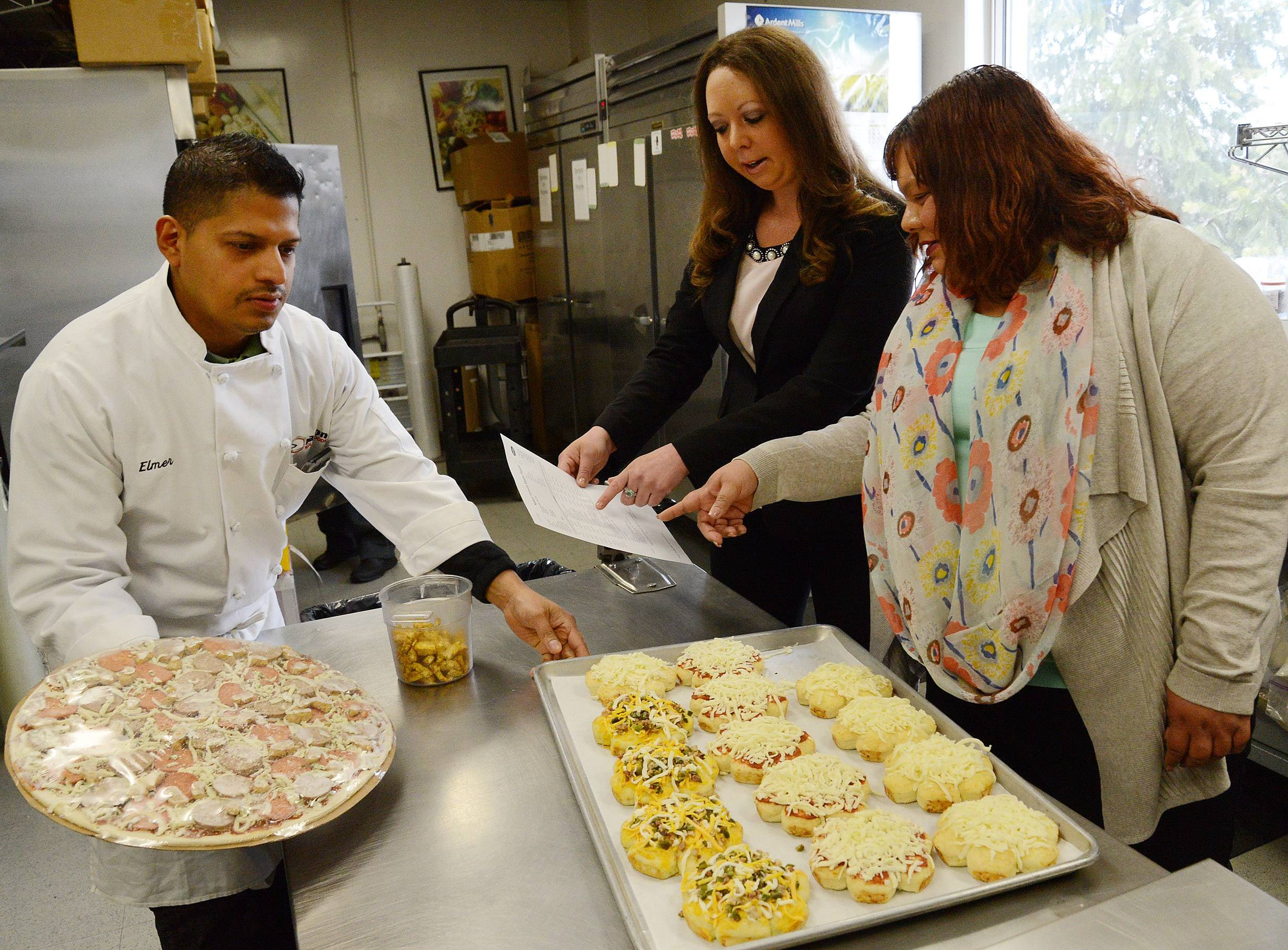 Harper College graduates Michelle Foerster and Melissa Ortega work with kitchen supervisor Elmer Garcia in the Nation Pizza and Foods test kitchen at the Schaumburg manufacturer.