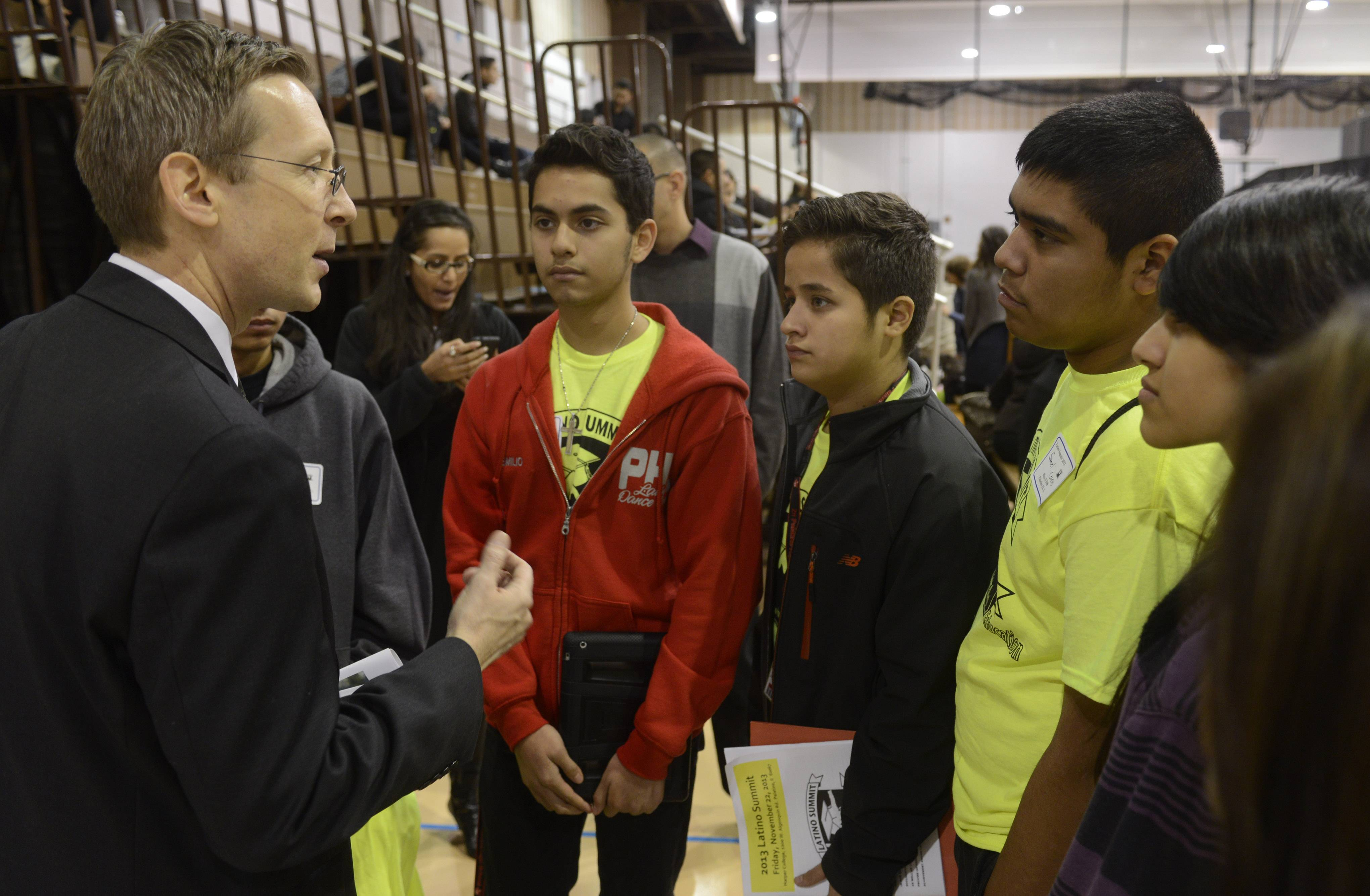 "Palatine-Schaumburg High School District 211 Superintendent Dan Cates, meeting with high schoolers at Harper College's 2013 Latino Summit, says Promise students must demonstrate ""dedicated and consistent effort, a willingness to be challenged and service to others."""