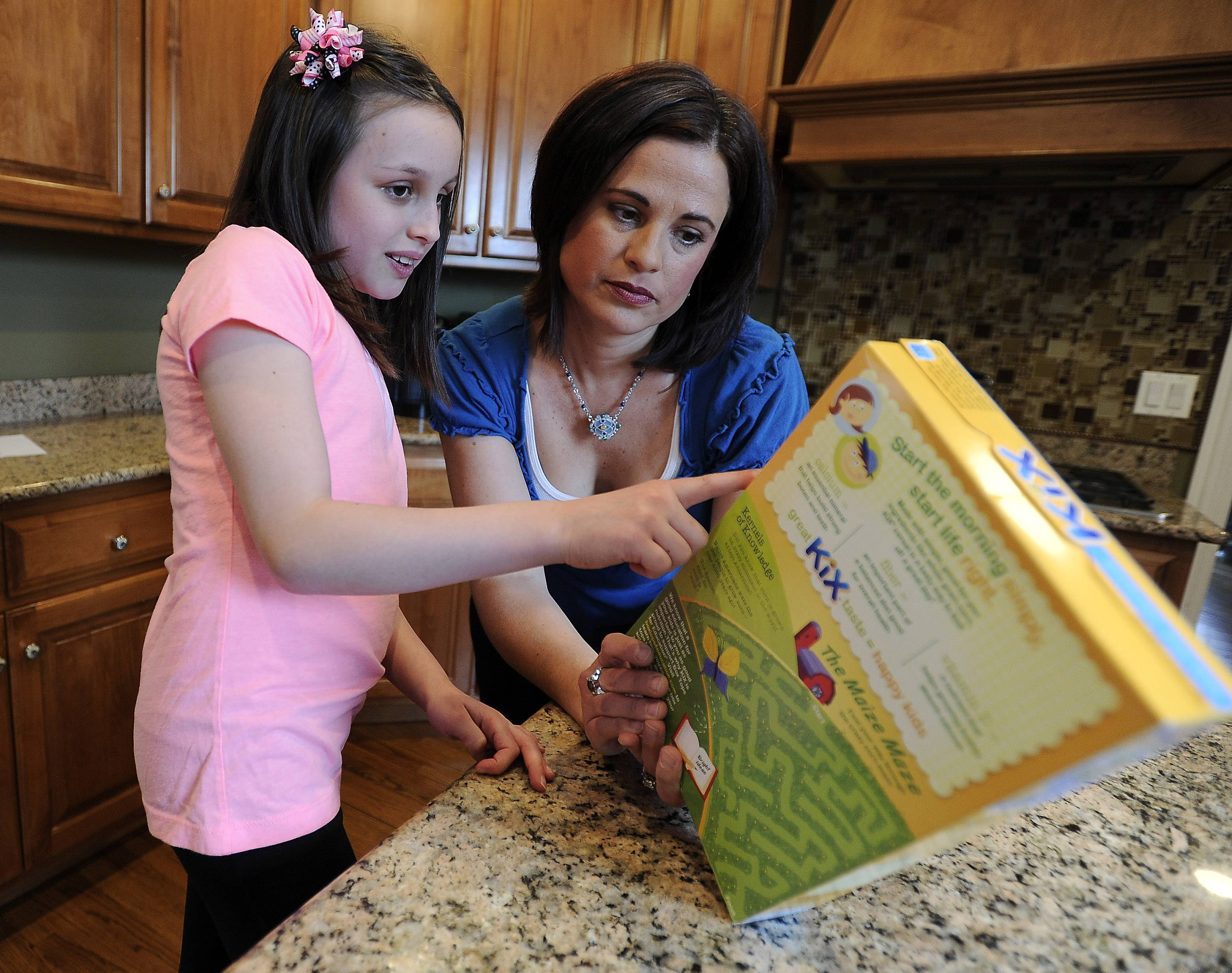 Lucca Teuscher, 8, and her mom Melissa check product ingredients before she eats anything to help Lucca avoid exposure to peanuts because of her life-threating allergy.
