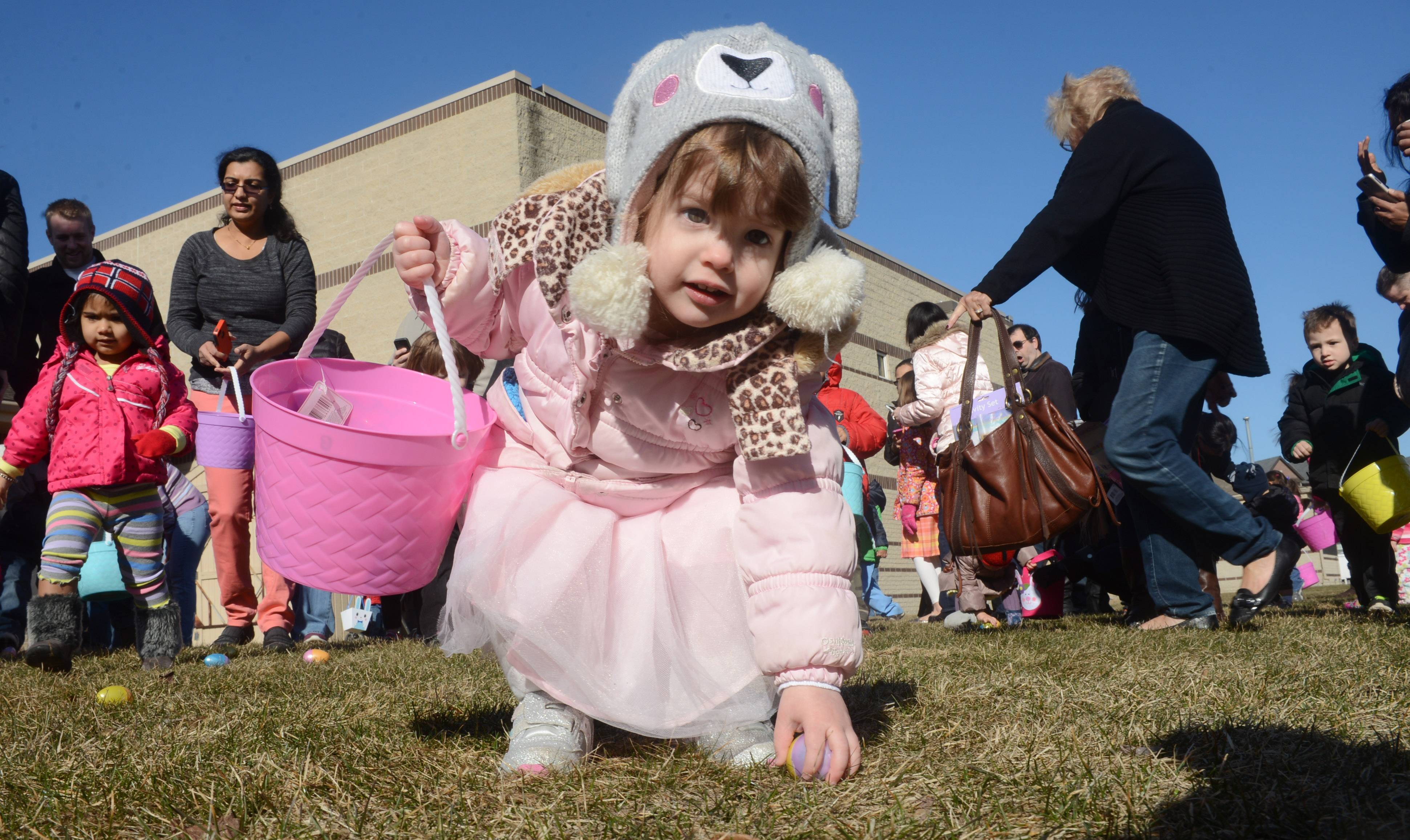 Lorelei Wheeler, 2, of Vernon Hills picks up plastic eggs during the Vernon Hills Park district Hoppin Holiday Hunt and Magic show at the Sullivan Community Center in Vernon Hills Saturday.