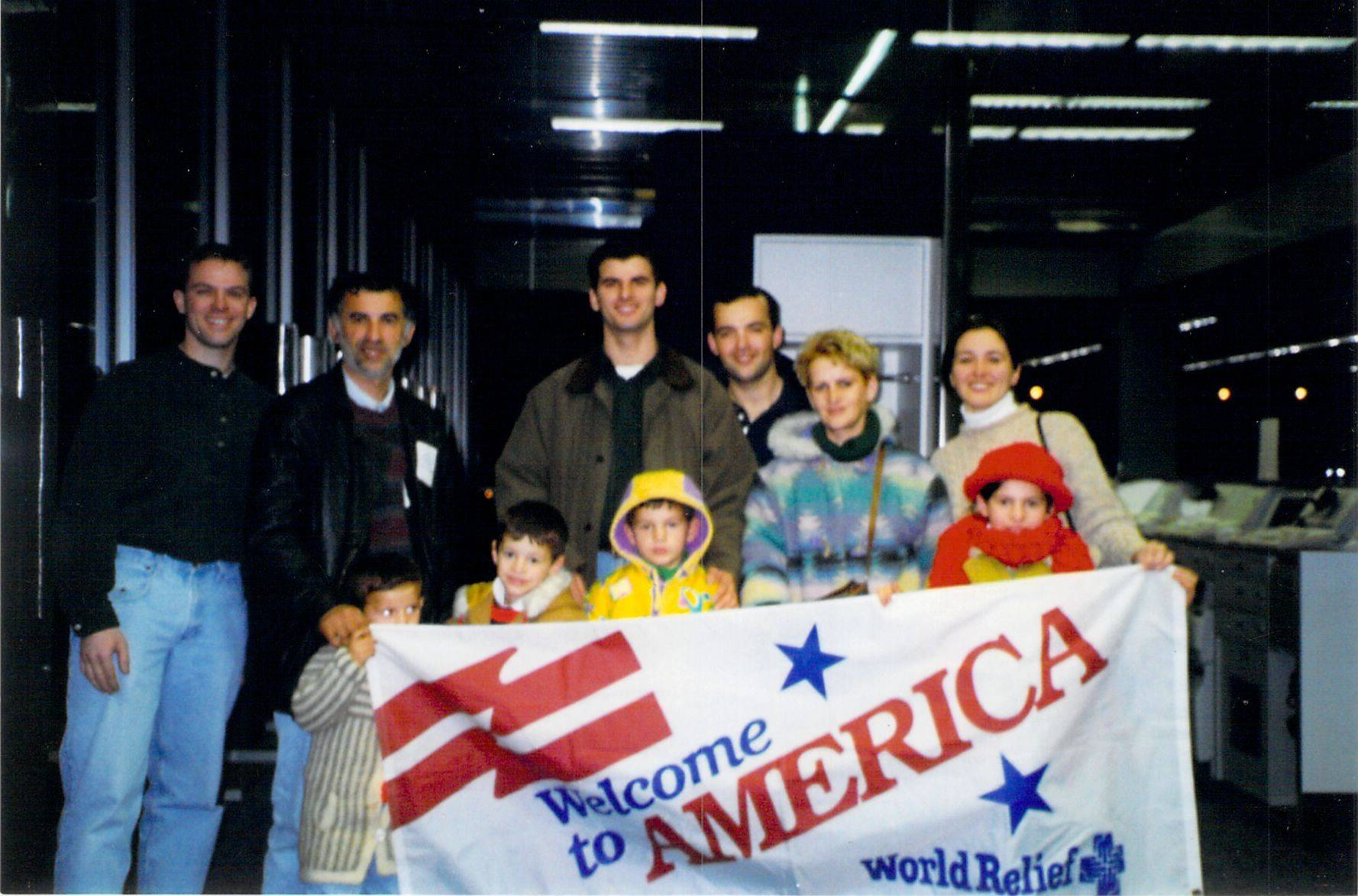 Hasan Fetahi's family, fleeing Kosovo, arrives in the U.S. in 2000 to live with the Aurand family, Virgil, far left, and Jody, far right, of Elgin. Hasan, who came with his parents, brothers and sister, is the second child from the left in the front row.