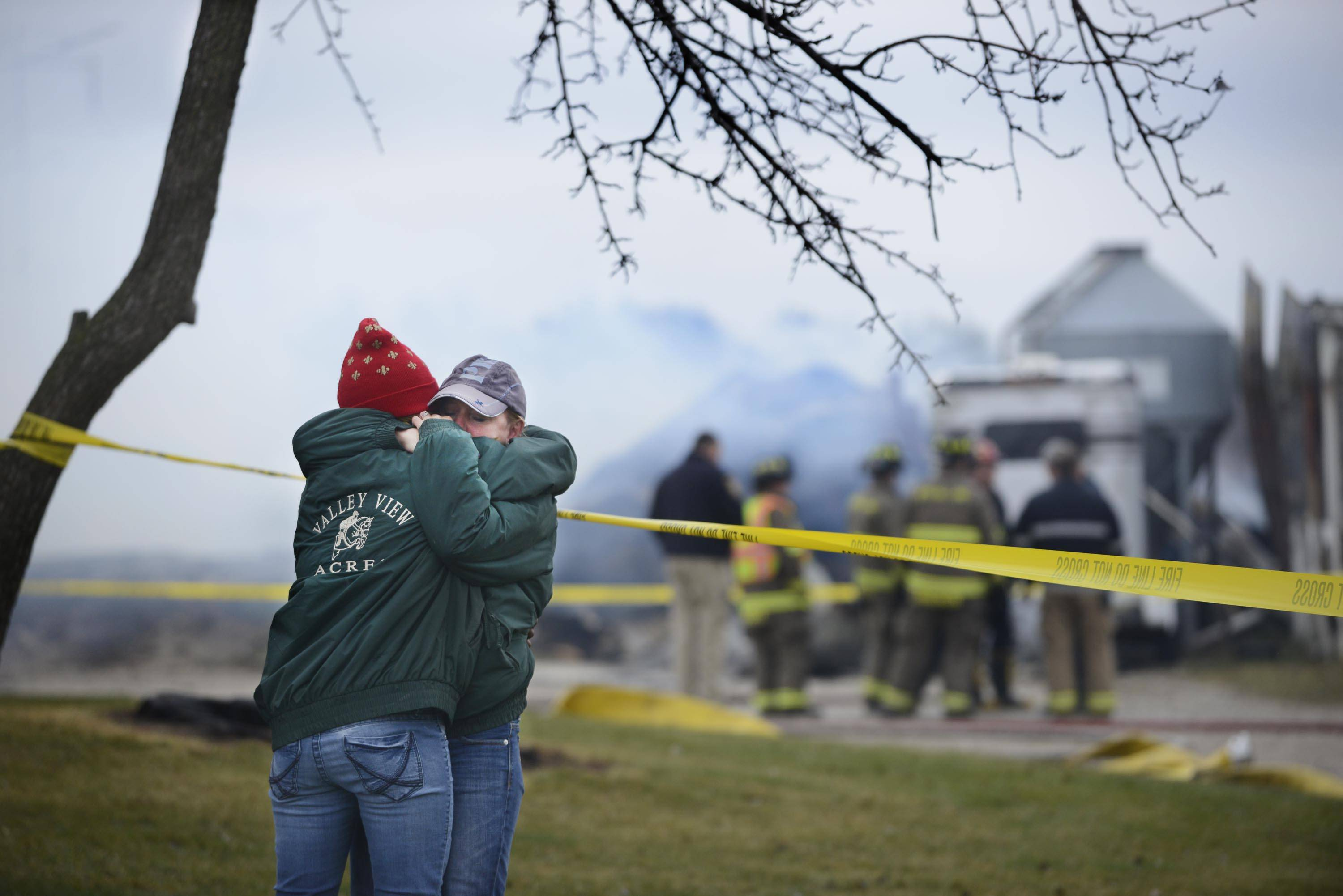 Owner Amber Bauman hugs a friend after a barn fire at Valley View Acres in unincorporated Crystal Lake killed 32 horses.