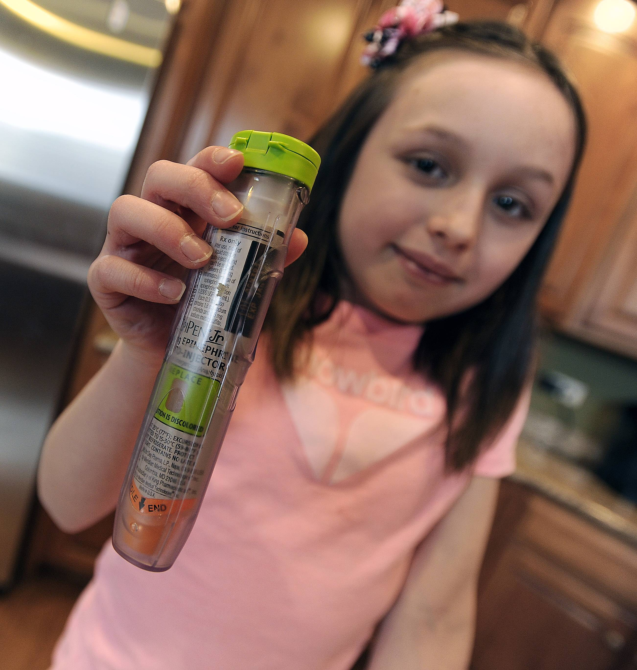 Lucca Teuscher, 8, holds up the Epinephrine pen she must use when she has an attack caused by her life-threatening peanut allergy.