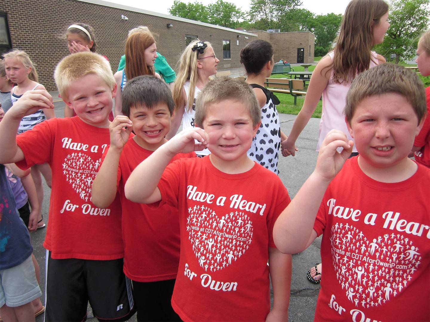 "Classmates at Evergreen Elementary School in Carol Stream show their support for Owen Payton (making an ""O"" with their hands) after his 2014 heart transplant."