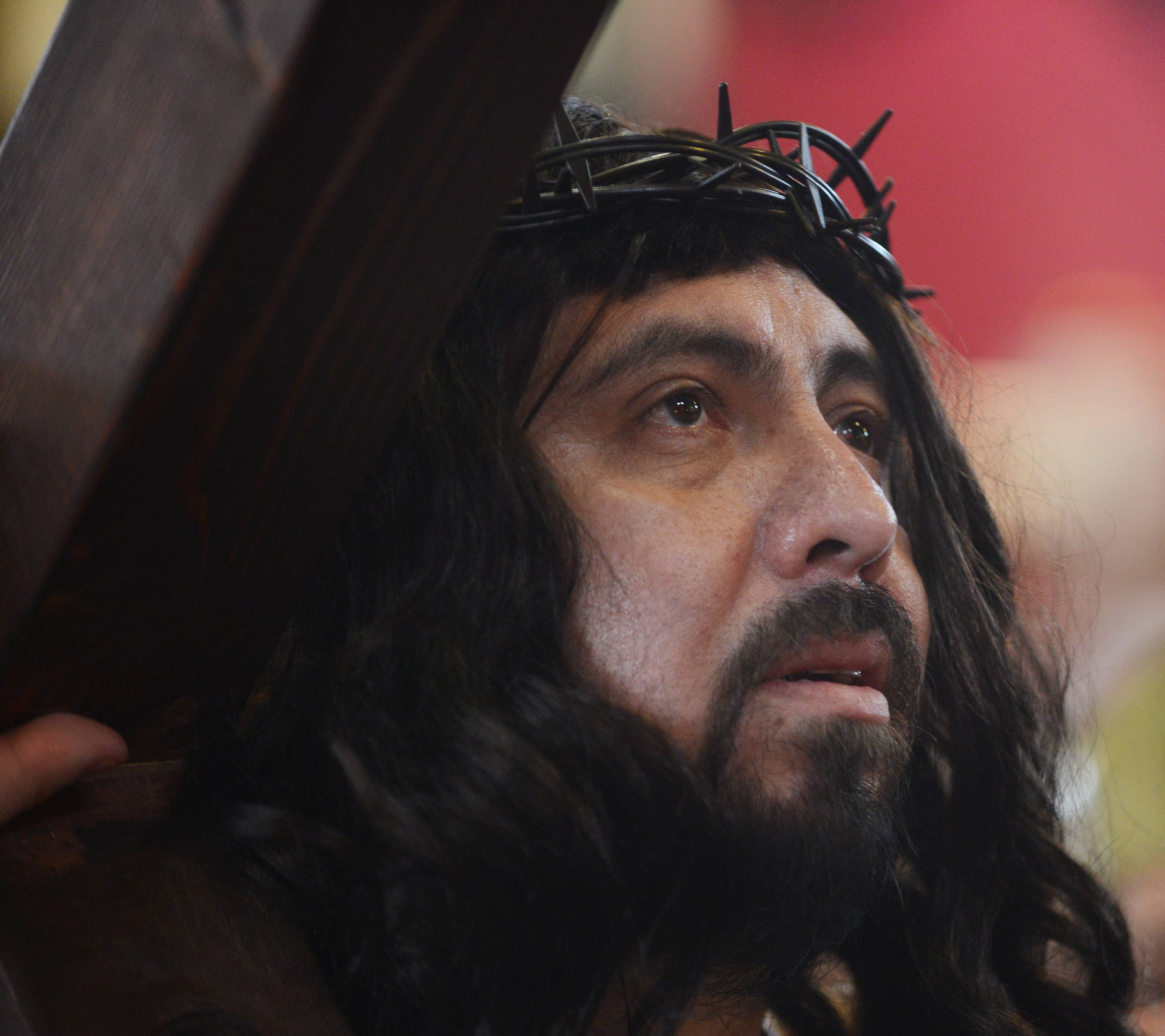 Jesus, played by Manuel Diaz, carries his cross during Via Crusis at Santa Maria del Popolo parish in Mundelein Friday.