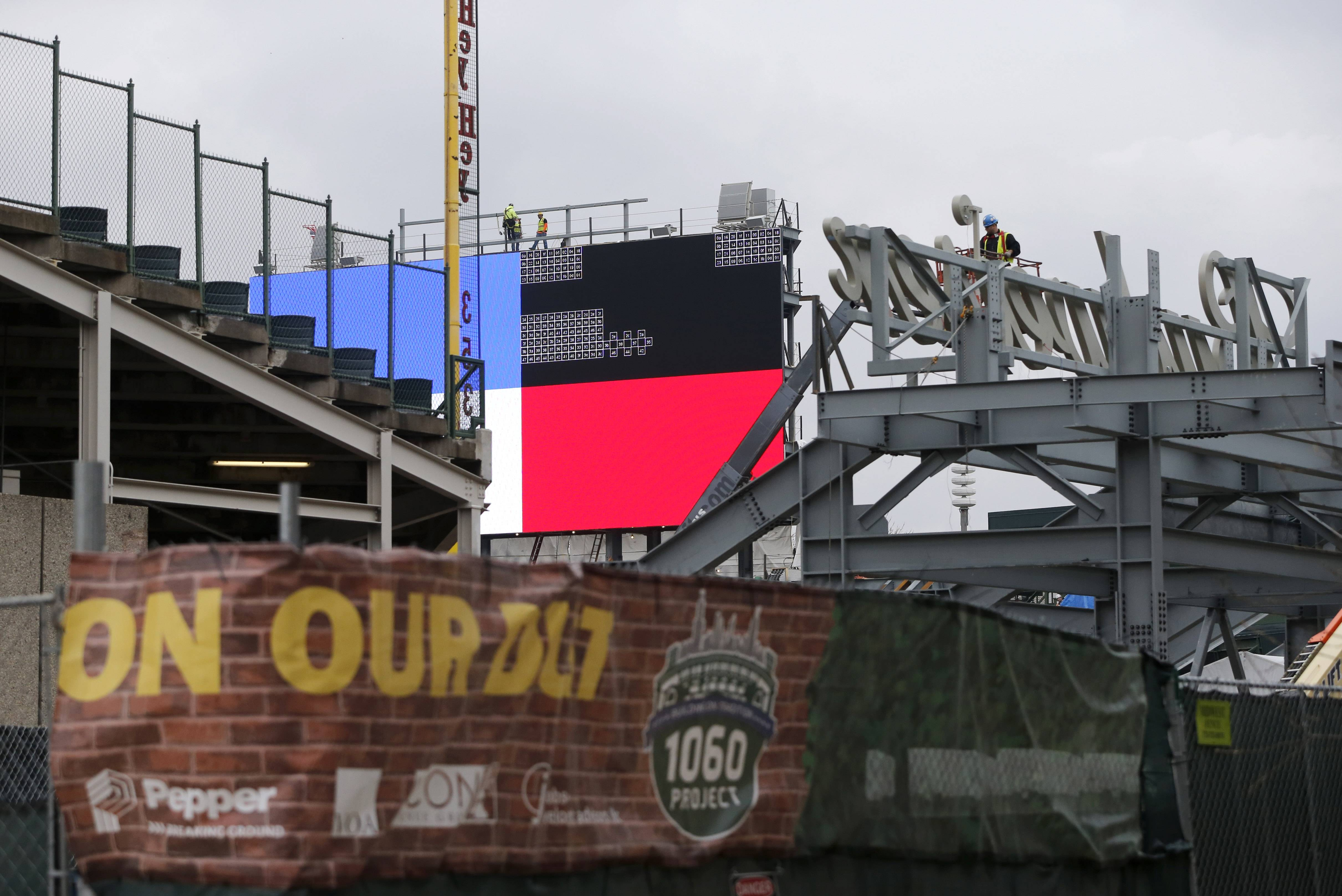 Construction continued on renovations to Wrigley Field Thursday including the installation of a Jumbotron above the left field bleachers, background, and a Budweiser sign in right field.