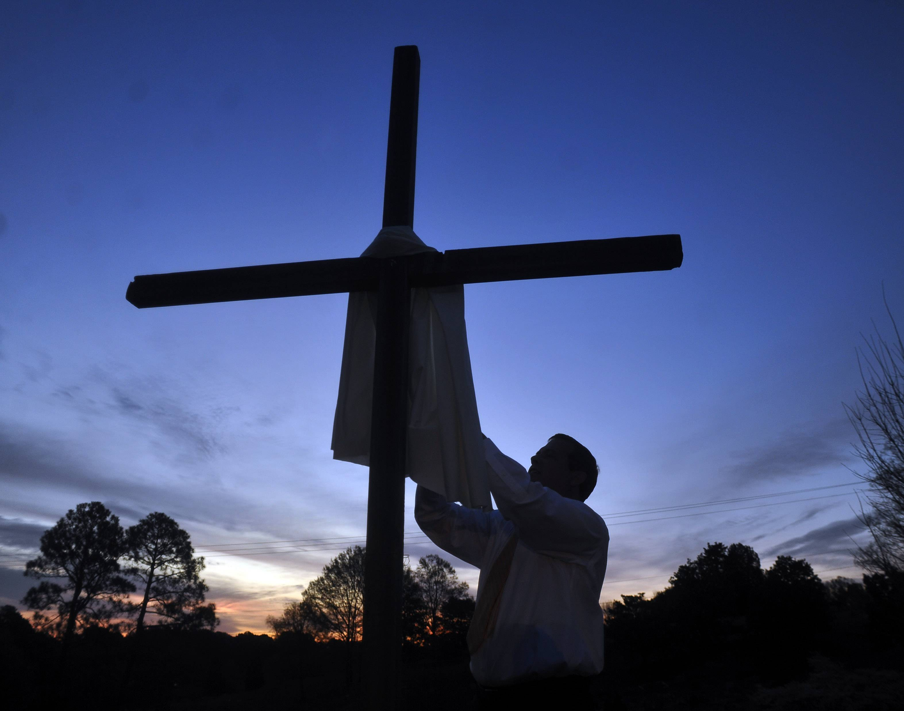 Rev. Bill Barksdale puts a cloth on a cross before the start of a Easter Sunday sunrise service at St. Andrew's United Methodist Church in Oxford, Miss. on Sunday, April 5, 2015.
