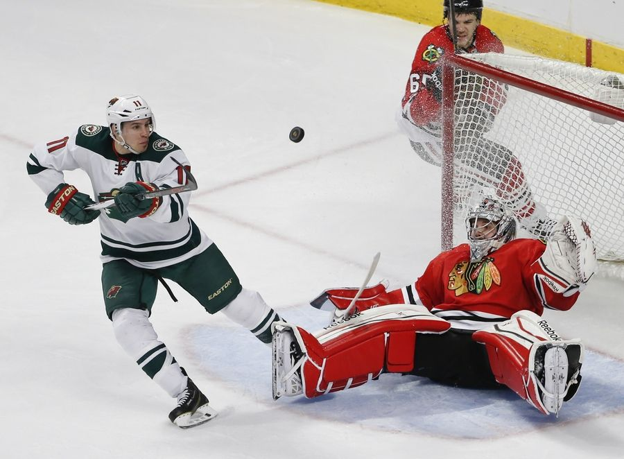Minnesota Wild left wing Zach Parise (11) tries to score against Chicago Blackhawks goalie Corey Crawford (50) during the third period of an NHL hockey game Tuesday, April 7, 2015, in Chicago. The Wild won 2-1.