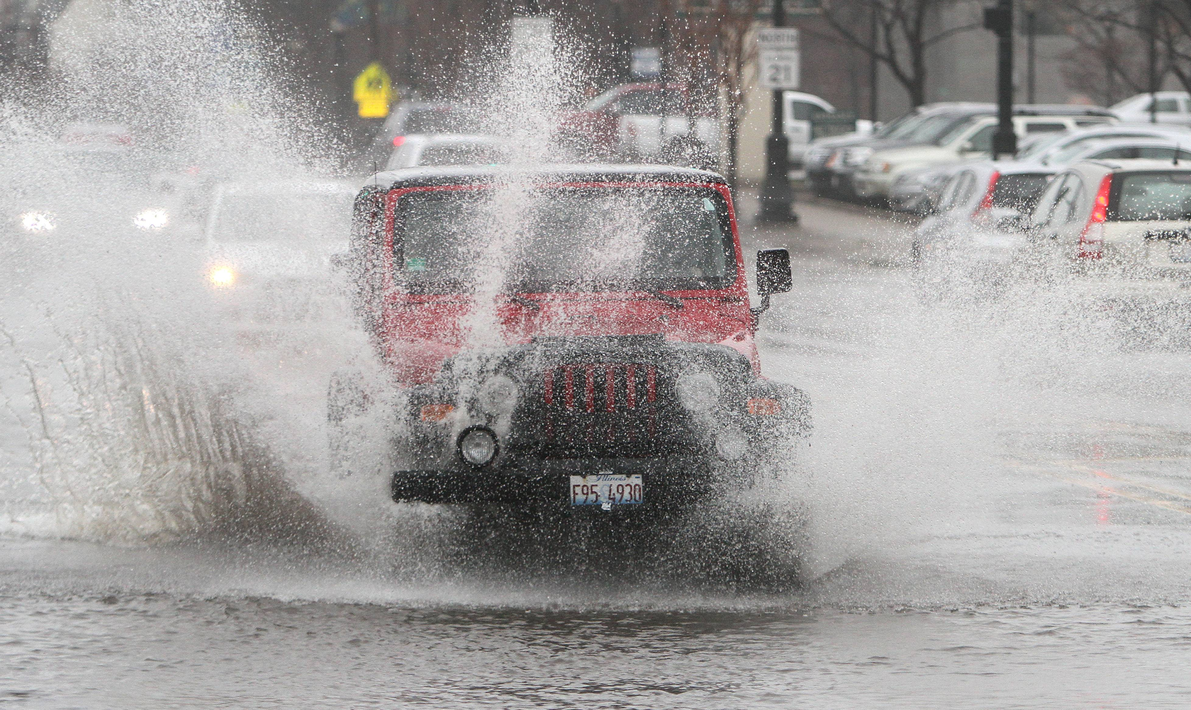 A driver bravely barrels through standing water on Milwaukee Ave. in Libertyville as heavy rains fell on the area Thursday morning.