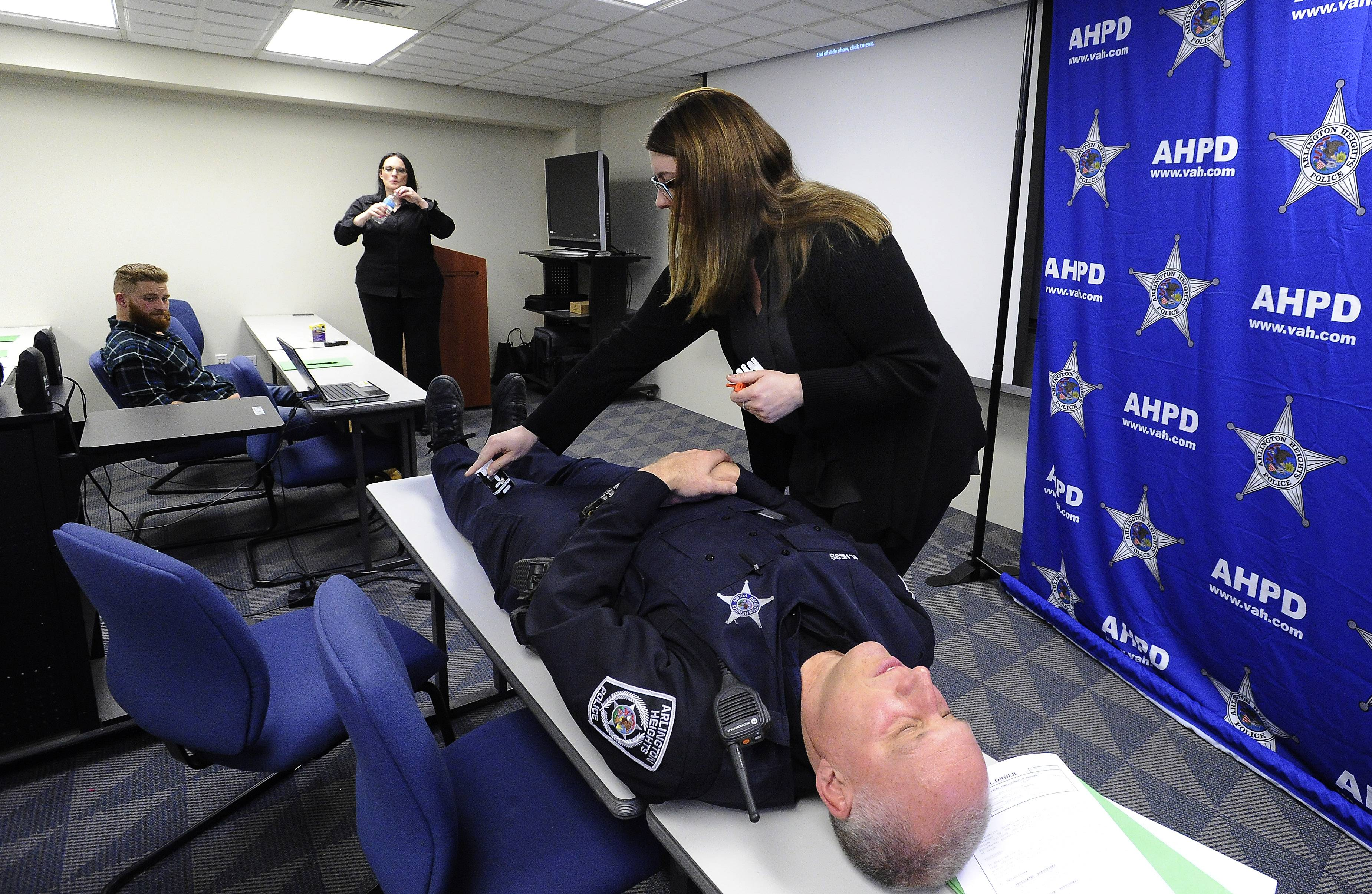Chelsea Laliberte, executive director/co-founder of Live 4 Lali organization, uses Arlington Heights police officer Bob Hess to show where to inject a heroin antidote.