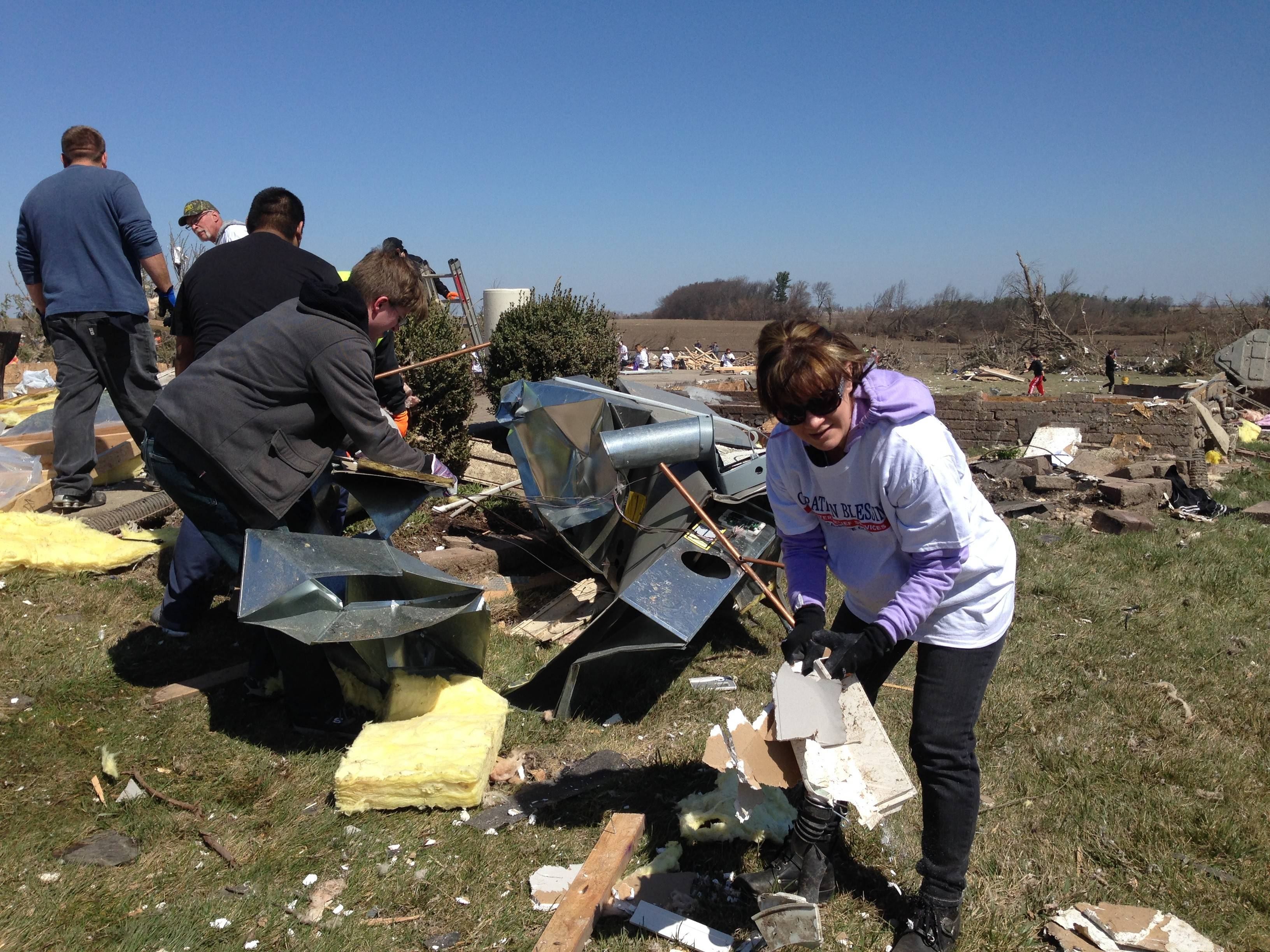 Volunteers assist in the cleanup of the tornado-destroyed home of Mike Price in Rochelle Saturday morning. Operation Blessing was one of many faith-based organizations that put out an open call for volunteers to help in the aftermath of Thursday's tornado that also hit the nearby town of Fairdale.