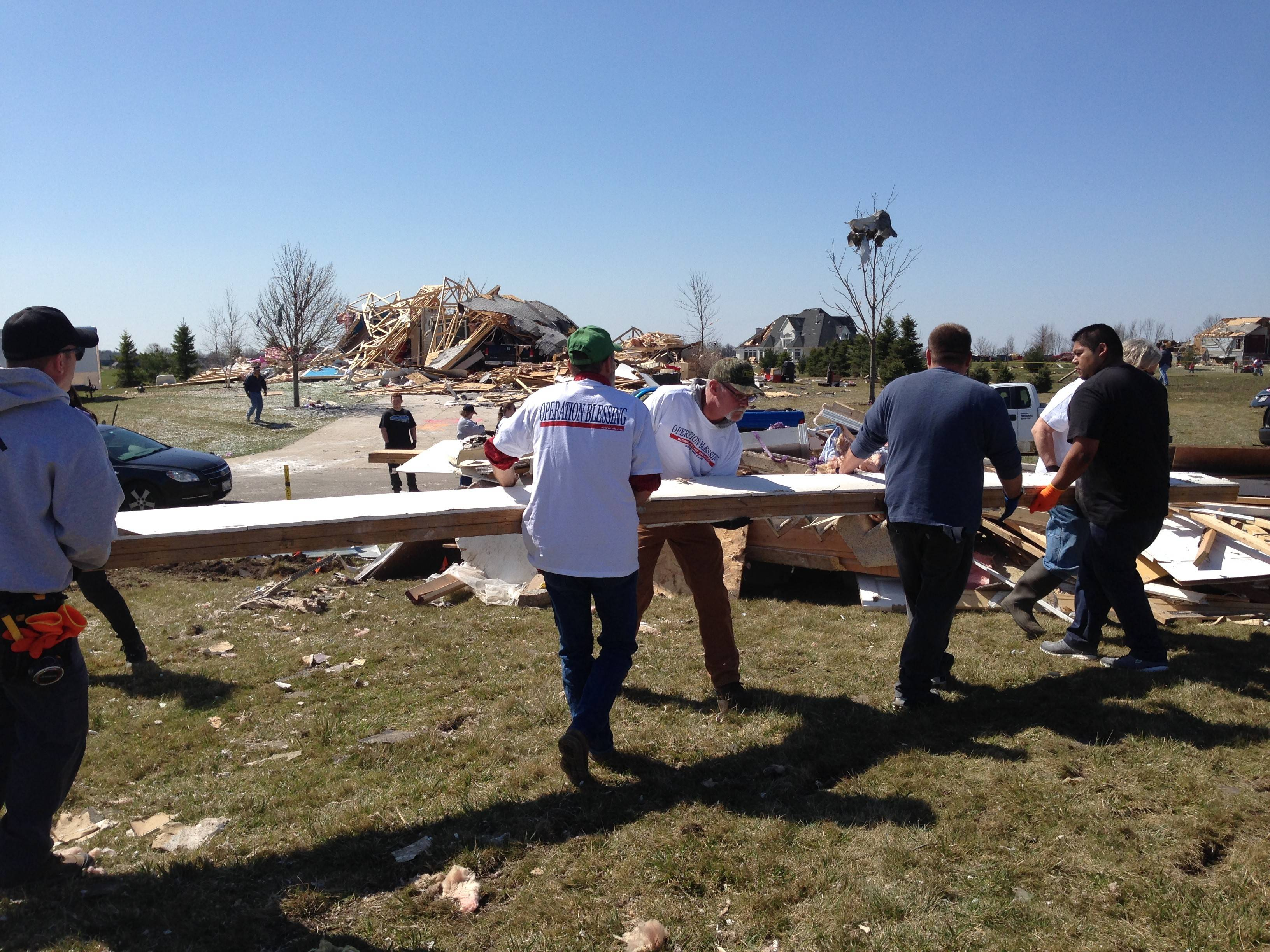 Volunteers assist in the cleanup of homes damaged and destroyed by last Thursday's tornado in Rochelle Saturday morning. Operation Blessing was one of many faith-based organizations that put out an open call for volunteers to help in the aftermath of Thursday's tornado that also hit the nearby town of Fairdale.