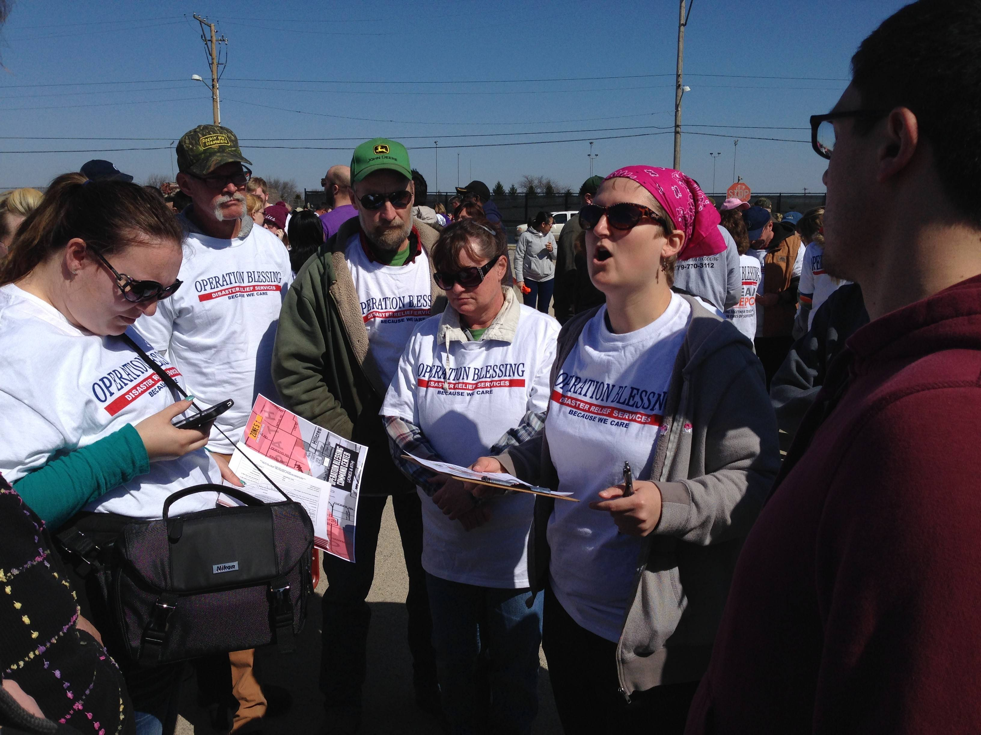 Hoffman Estates resident Lisa Creamer, in the pink bandanna, shares information with fellow volunteers who showed up Saturday morning for a post-tornado cleanup in Rochelle organized by the faith-based organization Operation Blessing.