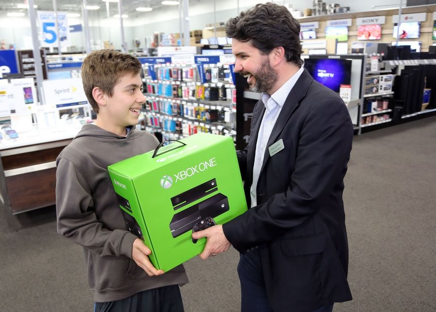 Sam Holtz, 12, of Hawthorn Woods hands Ryan Blackburn of Make-A-Wish Illinois an Xbox One on Thursday at the Best Buy in Deer Park Thursday. Sam received two game consoles from Best Buy after he completed an nearly perfect NCAA bracket in a contest but was disqualified because he was underage. Now he's been awarded a $20,000 scholarship by a weight loss company called ViSalus.