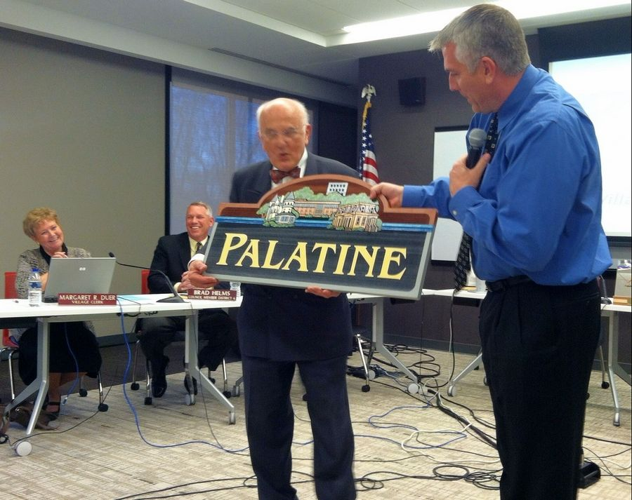 Hervé Boigeol, a delegate from Fontenay-le-Comte, accepts a gift from Palatine Mayor Jim Schwantz at Monday's village council meeting.