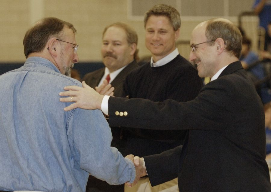 Athletic director Jim Kafer, far right, congratulates retired coach MIke Vandeveer for his induction in to the Geneva High School Athletics Hall of Fame Saturday during halftime of the Vikings boys basketball game with St. Charles East. Doug Reese, center left, who graduated in 1975 and Mark Searcy, 1981 were also inducted.