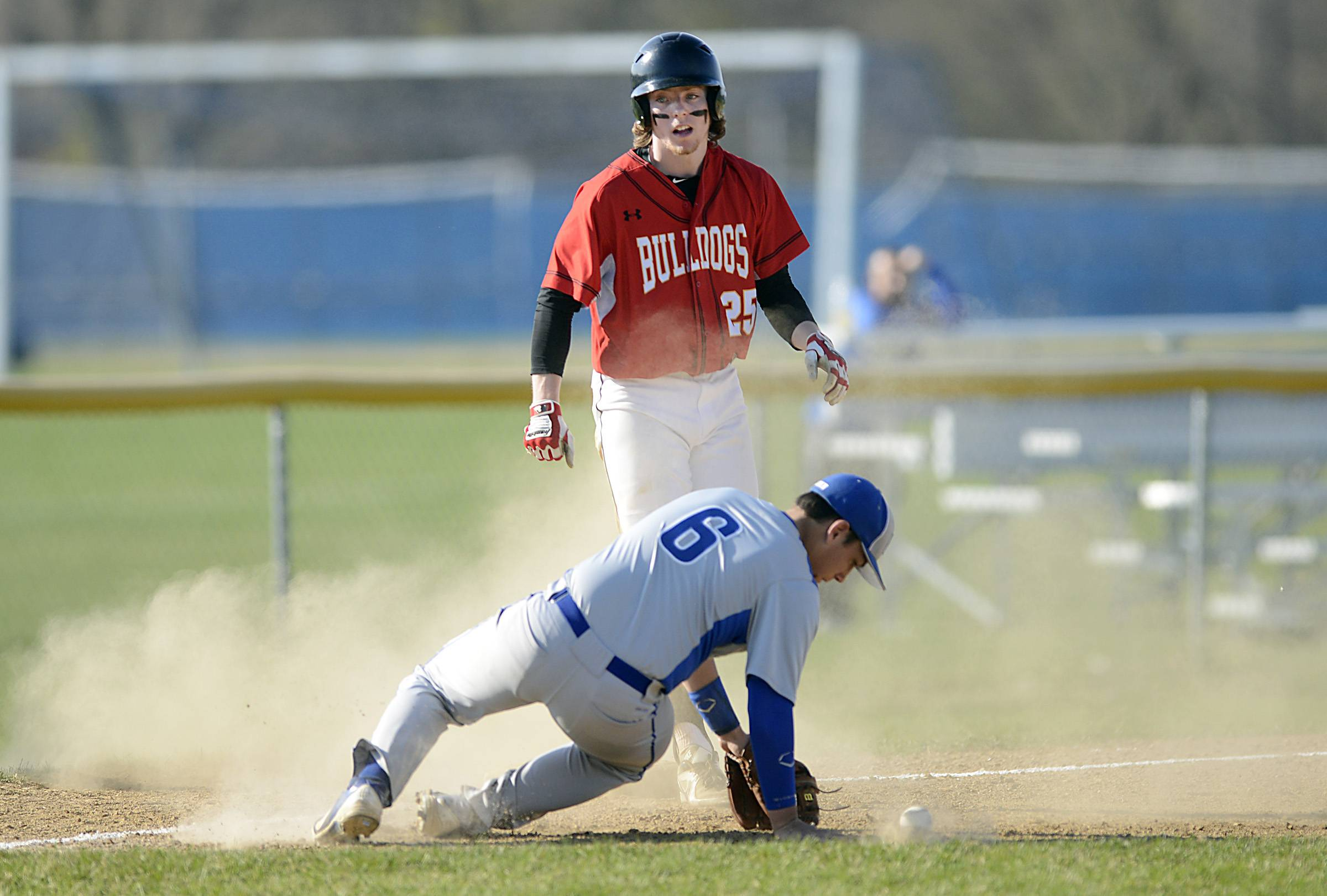Larkin third baseman Dan Lenz tries to field a throw from the outfield as Batavia's Steven Busby stands at the bag with a triple in the second inning Thursday in Elgin.