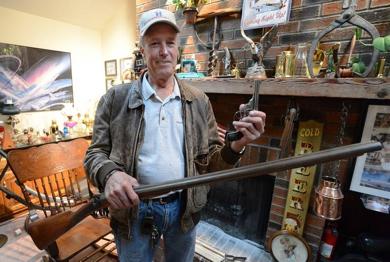 Art Lovi, holding one of his antique firearms, won his case and an $80,000 judgment against the Arlington Heights police on Thursday.