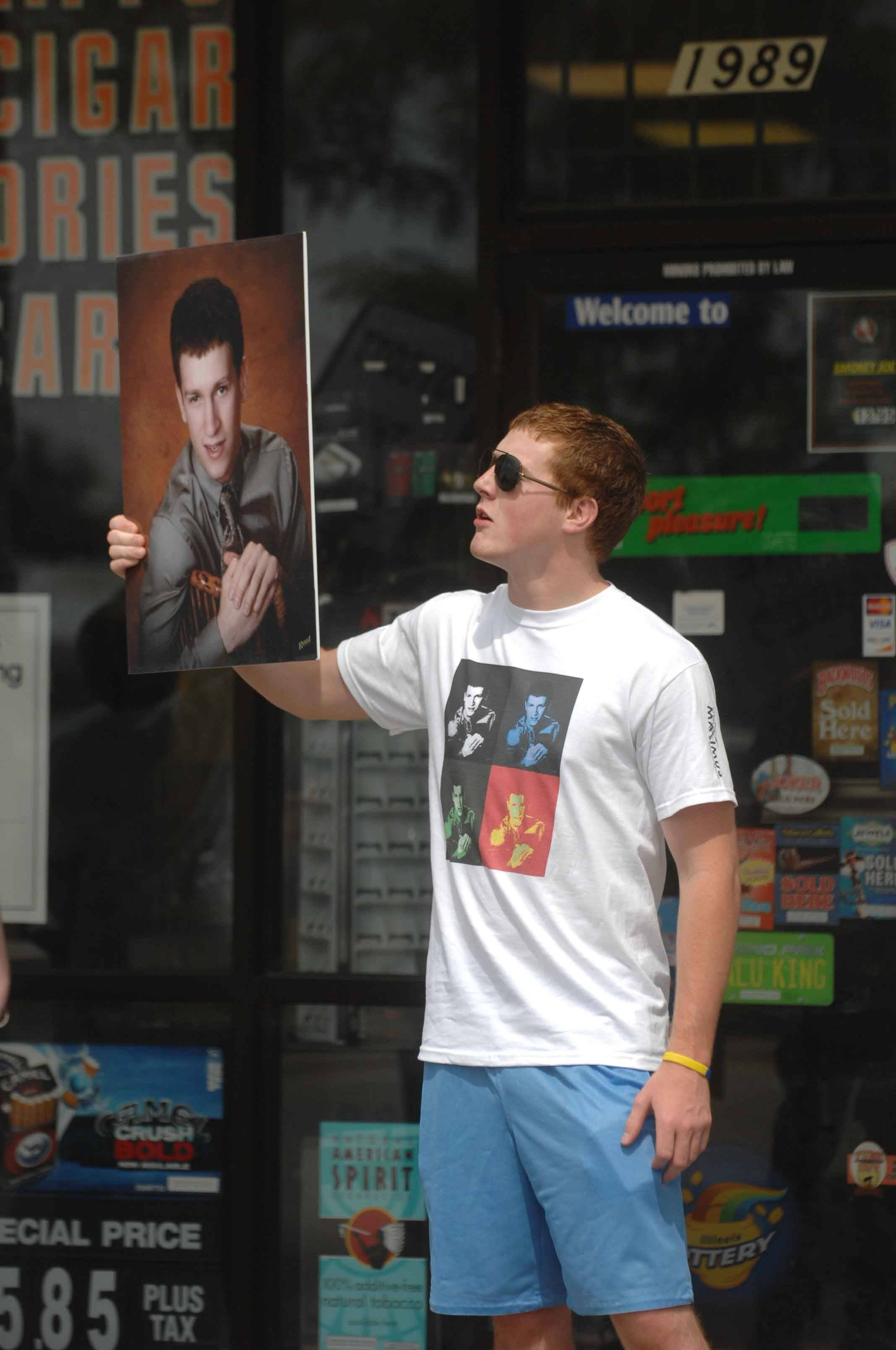 During a 2011 protest at an Aurora smoke shop, Sam McKinney holds a photo of his friend, Max Dobner, who died in a car crash after smoking fake marijuana.