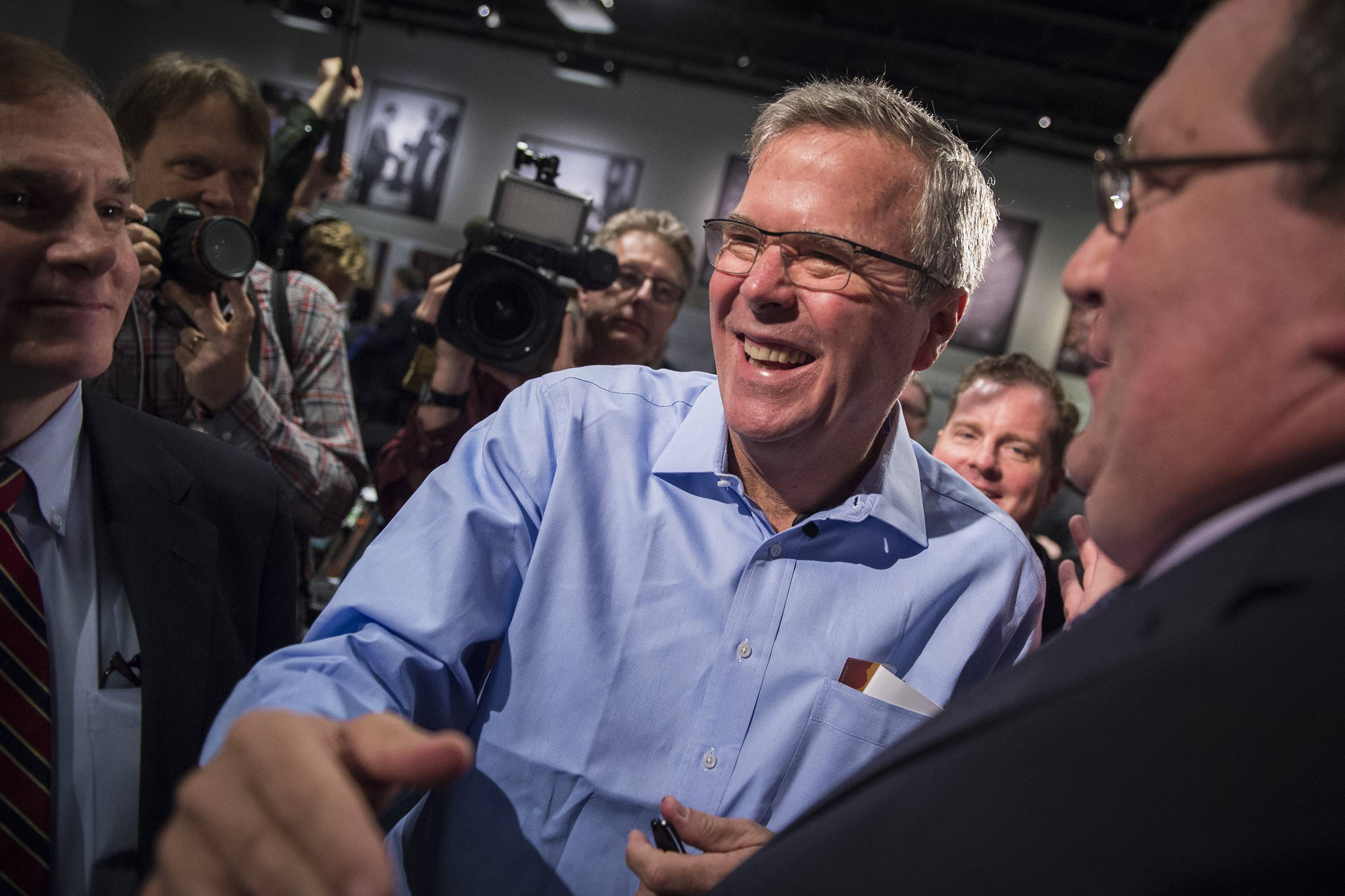 Florida Gov. Jeb Bush talks with patrons and signs autographs after speaking to a group at a Politics and Eggs event at The New Hampshire Institute of Politics in Manchester on Friday.
