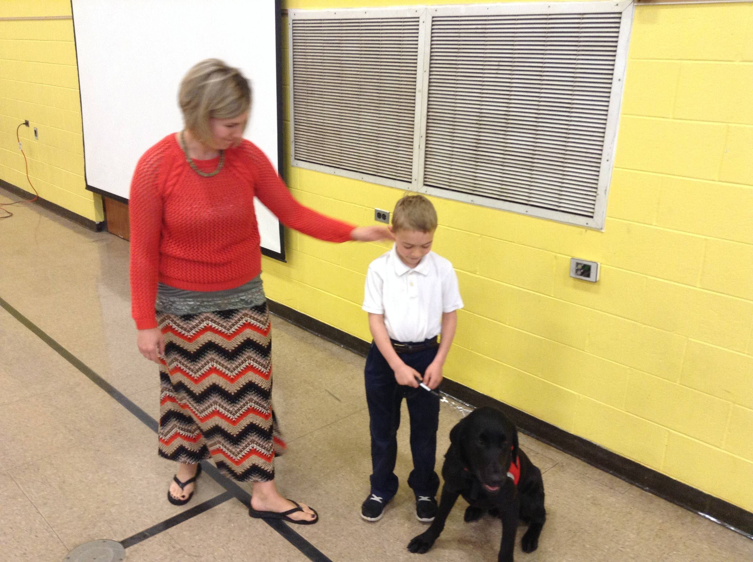 Rachel Gorman, her son, Aidan, and the boy's diabetes-alert dog, Chevy, participate in Friday's assembly at St. Mary of the Annunciation Catholic School in Fremont Township.