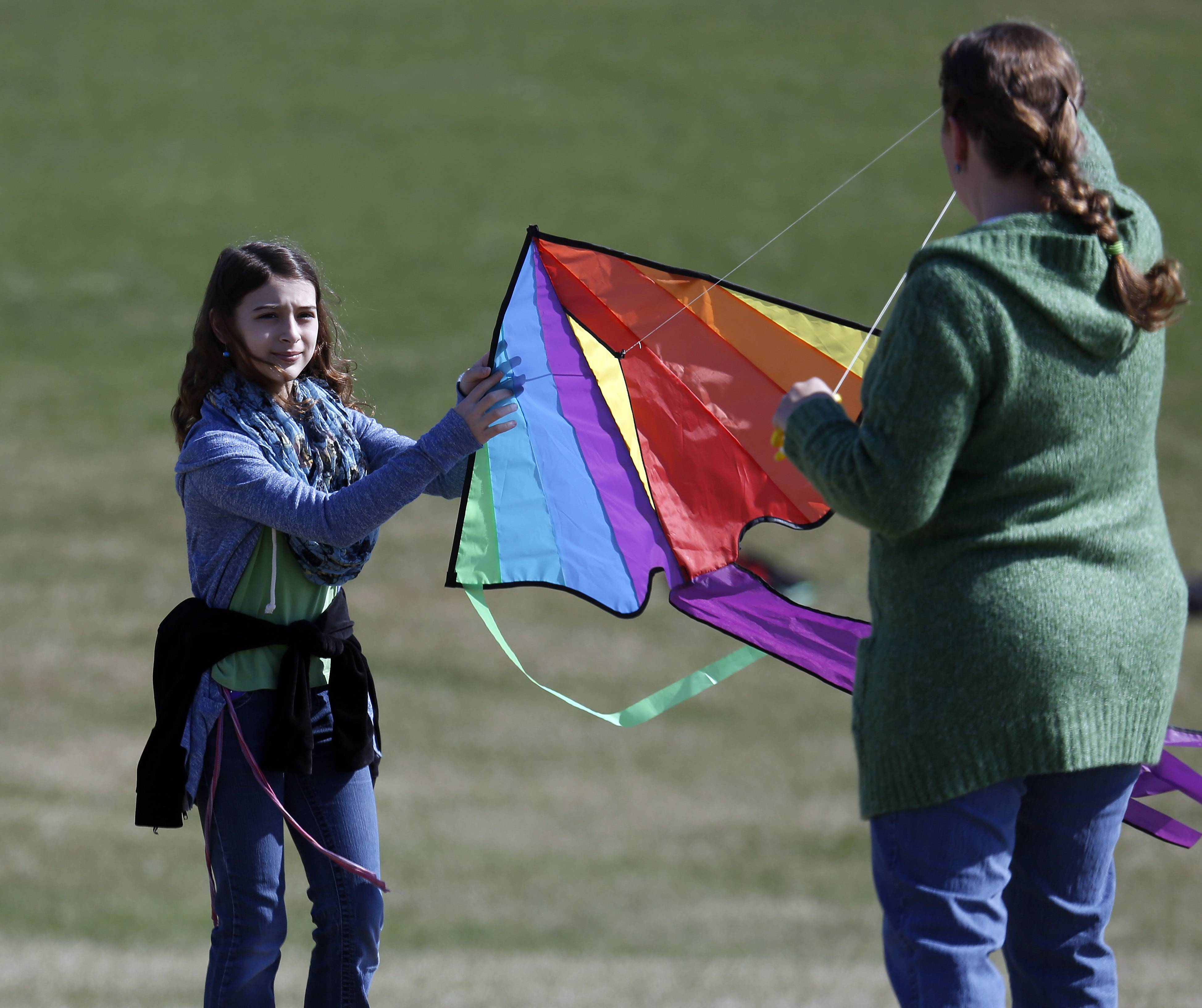 Hazel Kocher, 12, of Crystal Lake, gets some help launching her kite from her mom Jill Brown at Lions Park in Cary Saturday during the Illinois Association of Park Districts' statewide Flying 4 Kids celebration.