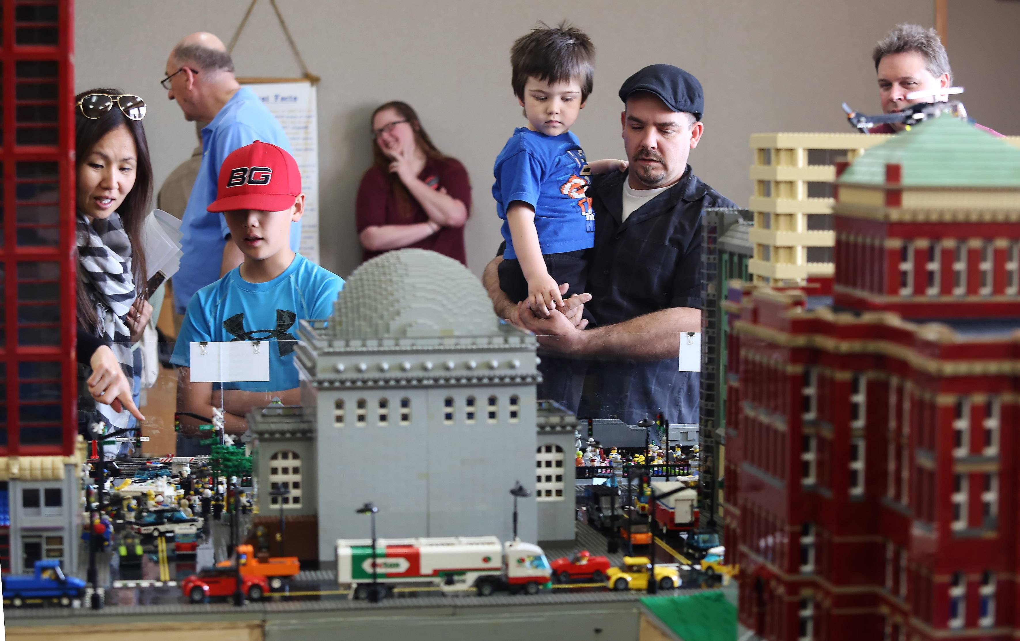 Adam Hyson of Lake in the Hills holds his son, Charlie, 4, as they watch the train at the Northern Illinois Lego Train Club exhibit Sunday at the Ela Area Public Library. Visitors enjoyed imaginative scenes and huge city landscapes made in Lego's while trains raced around on their tracks.
