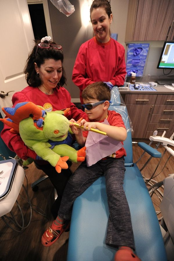 Dr. Victoria A. Ursitti, a pedicatric dentist, uses a puppet with big teeth to ease any fears of patient Filip Dinca, 4, of Buffalo Grove during his office visit as dental assistant Lina Sanchez looks on.