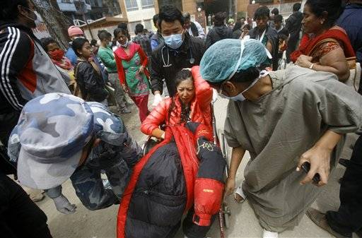 A Japanese tourist is taken on a wheelchair to a hospital after she was evacuated from Mount Everest Base Camp, in Kathmandu, Nepal, Sunday, April 26, 2015. The first group of survivors from an earthquake-triggered avalanche that swept through the Mount Everest base camp were flown to Nepal's capital on Sunday and taken to hospitals. Of those evacuated, 12 were Nepalese Sherpas. There was also one person each from China, South Korea and Japan. (AP Photo/Bikram Rai)