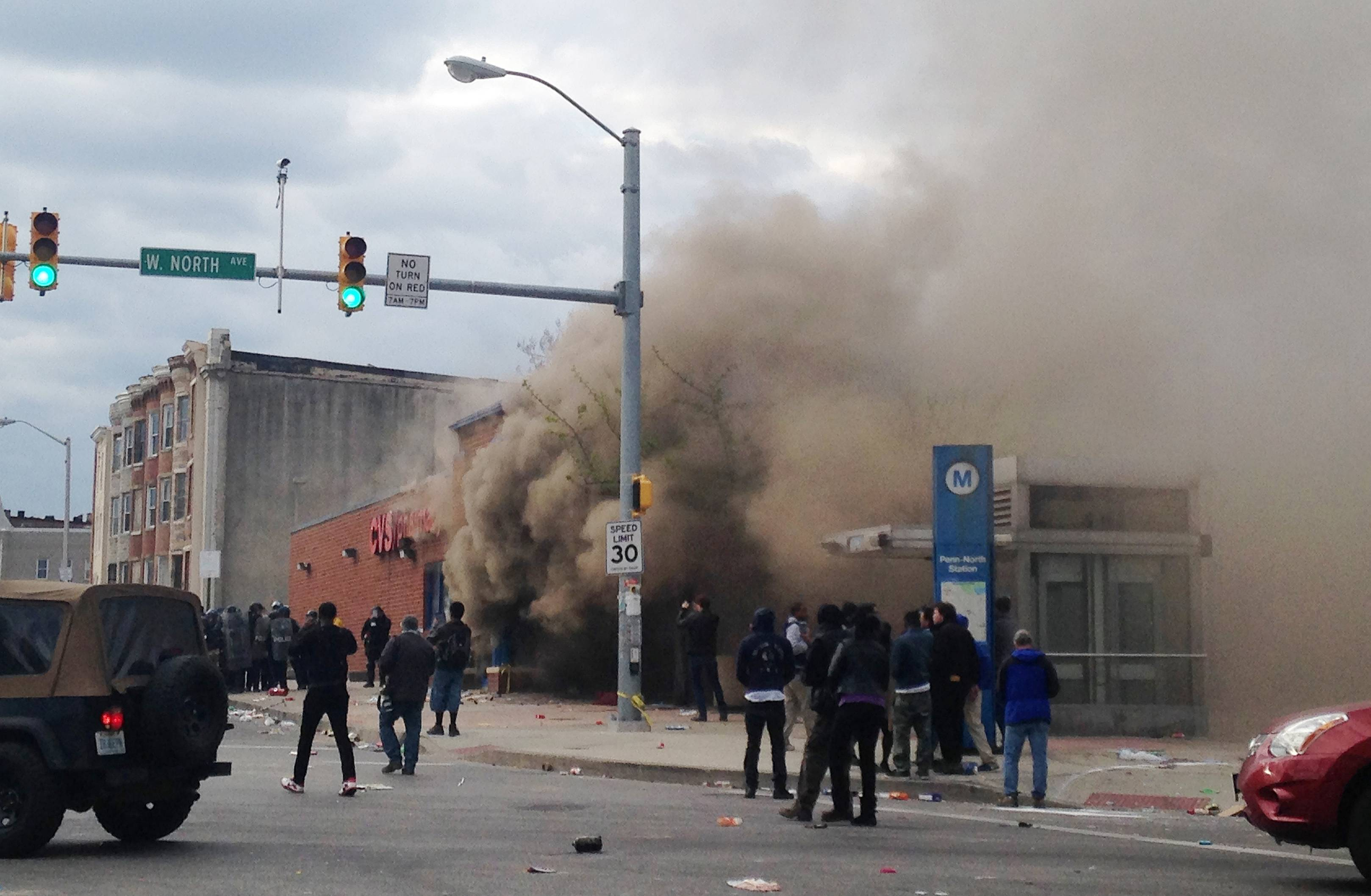 Firefighters battle a blaze at a construction site Monday after rioters plunged part of Baltimore into chaos, torching a pharmacy, setting police cars ablaze and throwing bricks at officers.