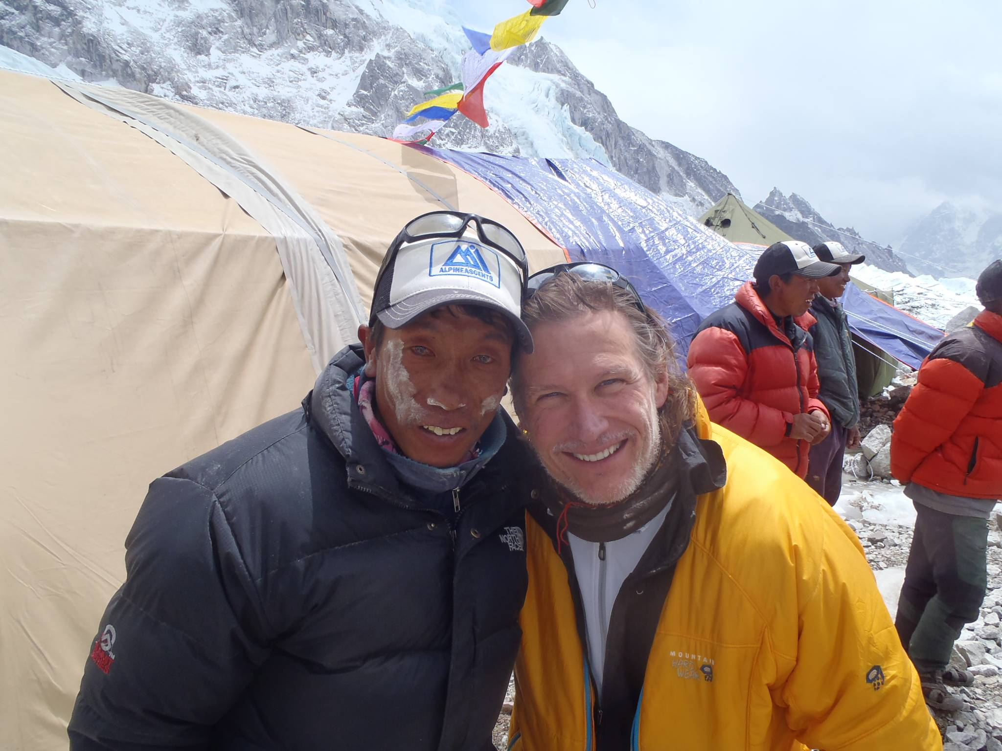 With white rice powder on his face from a 2014 puja ceremony blessing the next day's planned climb of Mount Everest, Sherpa Passang Therker, who survived last year's deadly avalanche, poses with climber Joel Schauer of Hawthorn Woods.