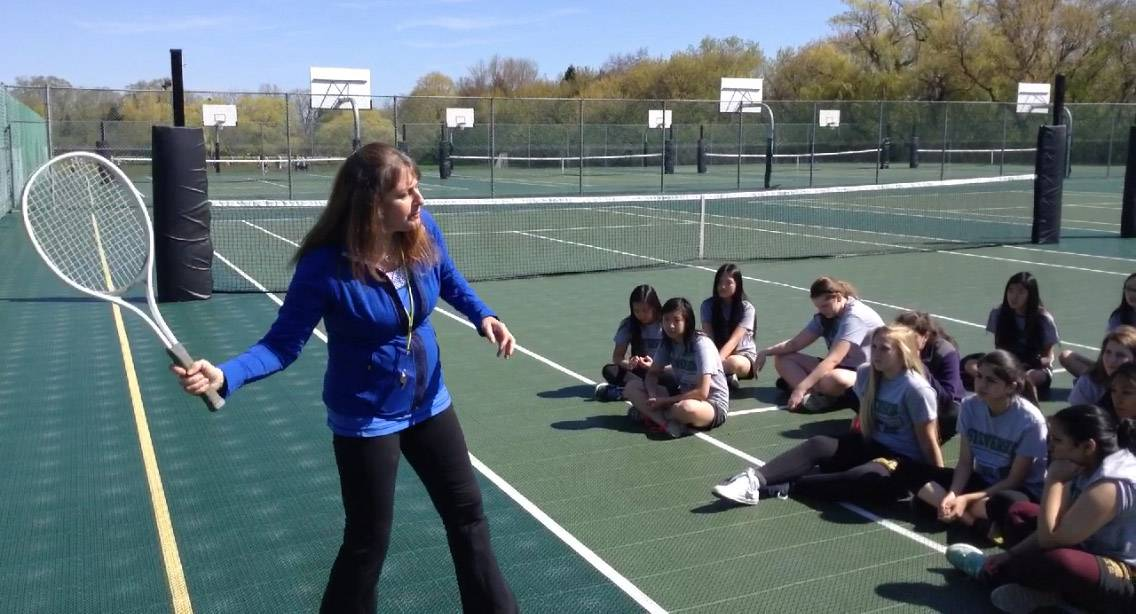 Stevenson High School P.E. teacher Vicky Nordhem, left, demonstrates a proper tennis swing to students Thursday at the Lincolnshire campus.