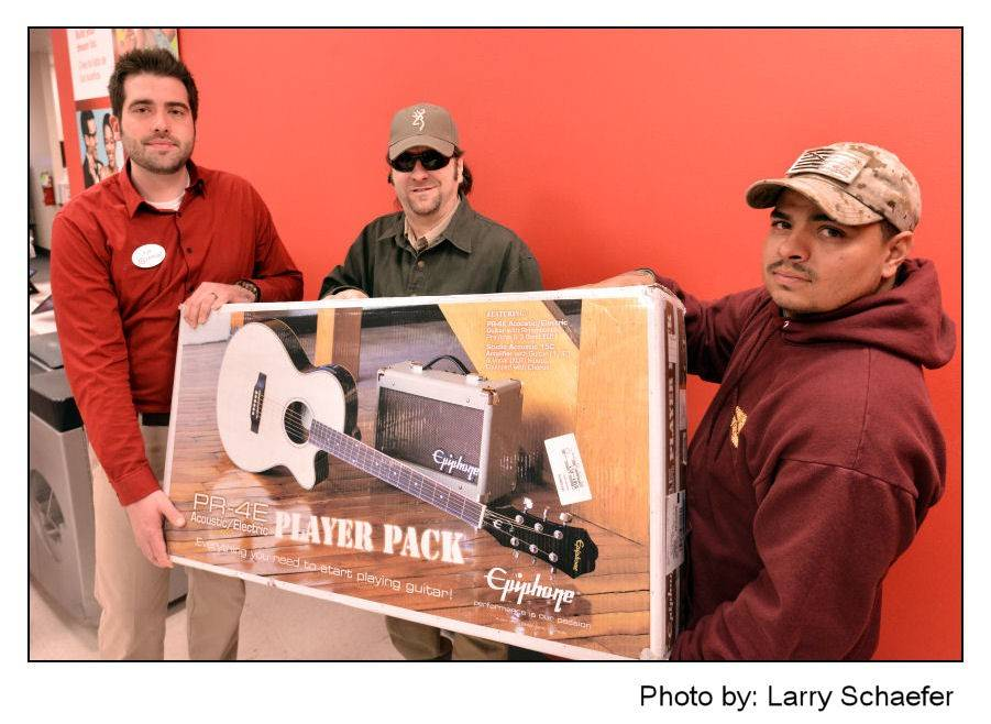 Palatine Target manager Kyle Dafcik, from left, musician and teacher Eric Kinkel of Palatine, and Jeremy Renteria, a Navy veteran who was selected for the Giving Back program, where Kinkel provides free music lessons and Target provided a free guitar package.