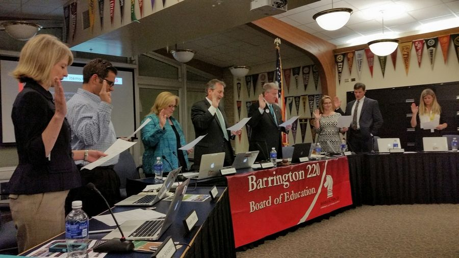 District 220 Superintendent Brian Harris, fourth from right, swears in the members of the school board Tuesday night.