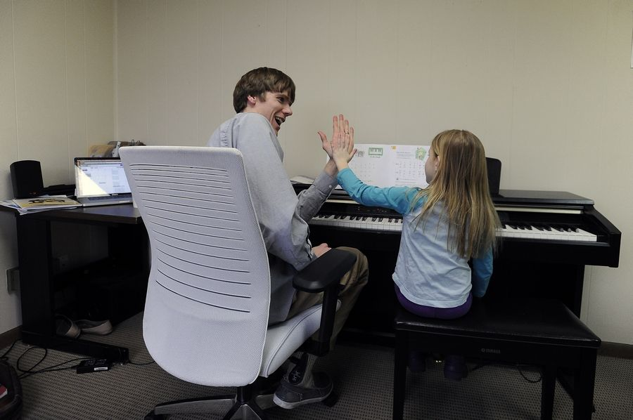 Brown high-fives 5-year-old piano student Katherine Monticello, of Wheaton. He teaches piano, flute, clarinet and other instruments, along with the saxophone.
