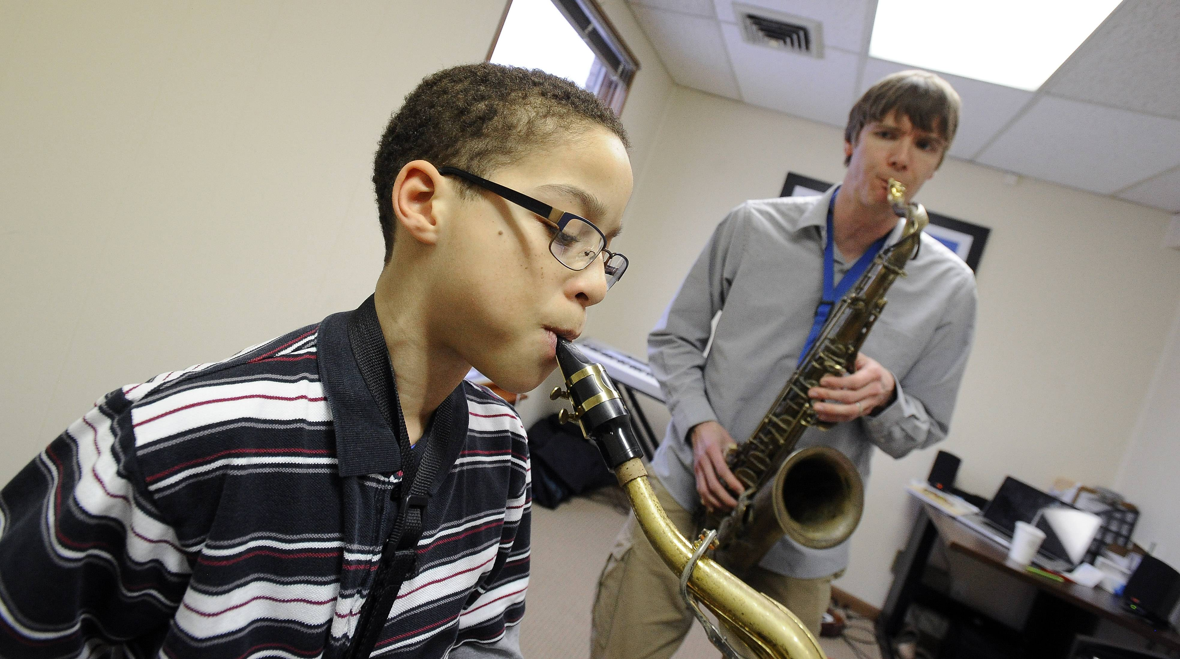 Mark Welsh/mwelsh@dailyherald.comJacob Horn, 11, of Wheaton takes sax lessons from Brown.