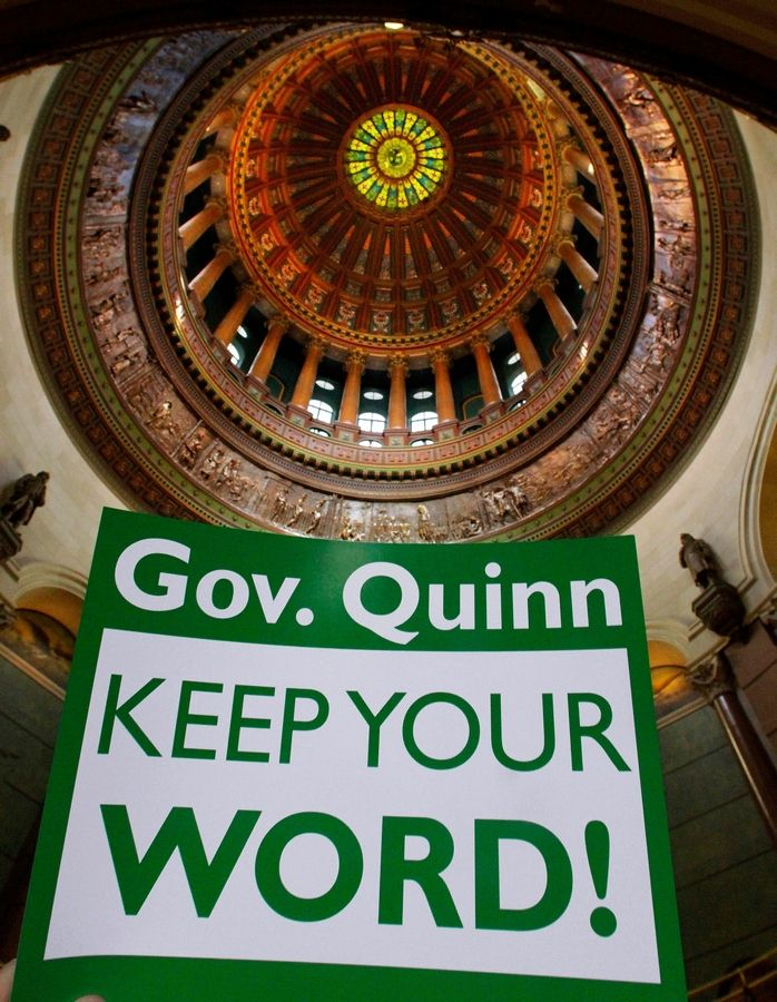 A sign held up by a member of the American Federation of State, County and Municipal Employees union is framed by the Illinois Capitol rotunda.