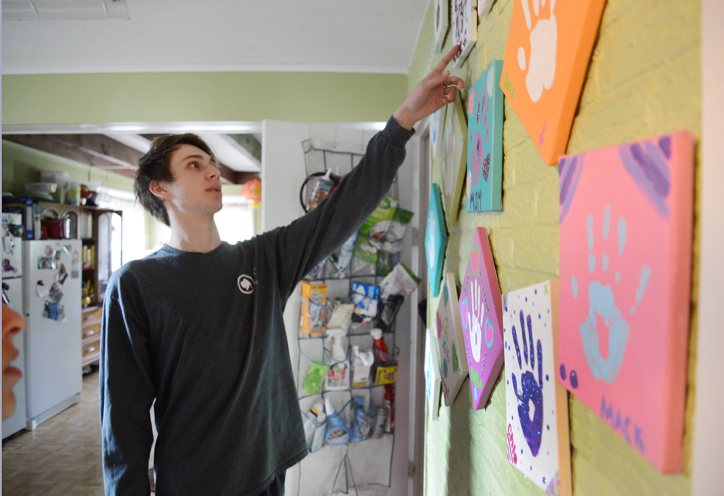 Chris Przybylo shows the handprints he and his friends made, which are now displayed on his family's kitchen wall.