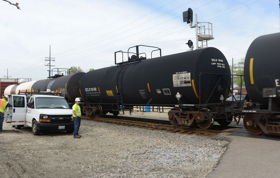 Tank cars with placards indicating they could be carrying potassium hydroxide, a corrosive, cross Lake-Cook Road in Barrington.
