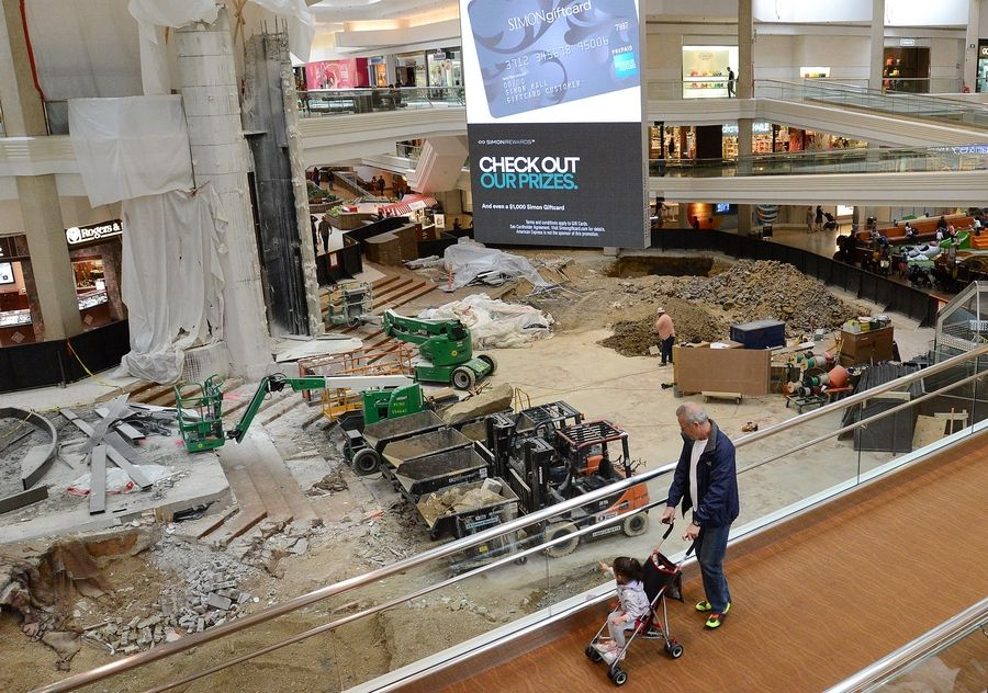 Krimo Kalache of Schaumburg, and his granddaughter Lilly, view from a ramp the construction in the center court area of Woodfield Mall. The $13.9 million renovation is on schedule for completion shortly before the holiday shopping season, mall management says.