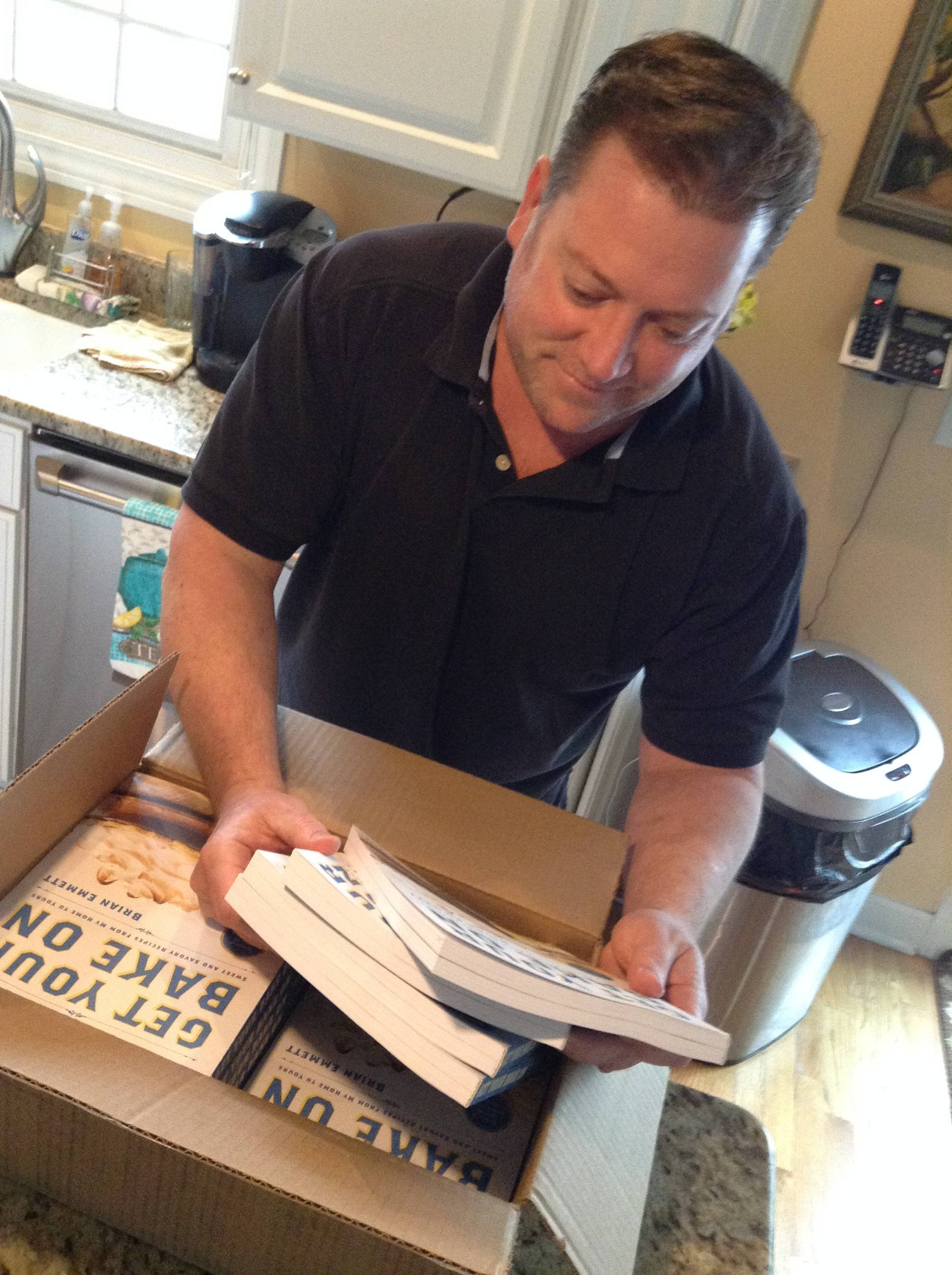 "Brian Emmett unpacks a box of his fresh-off-the-presses cookbook, ""Get Your Bake On,"" in his Itasca kitchen."